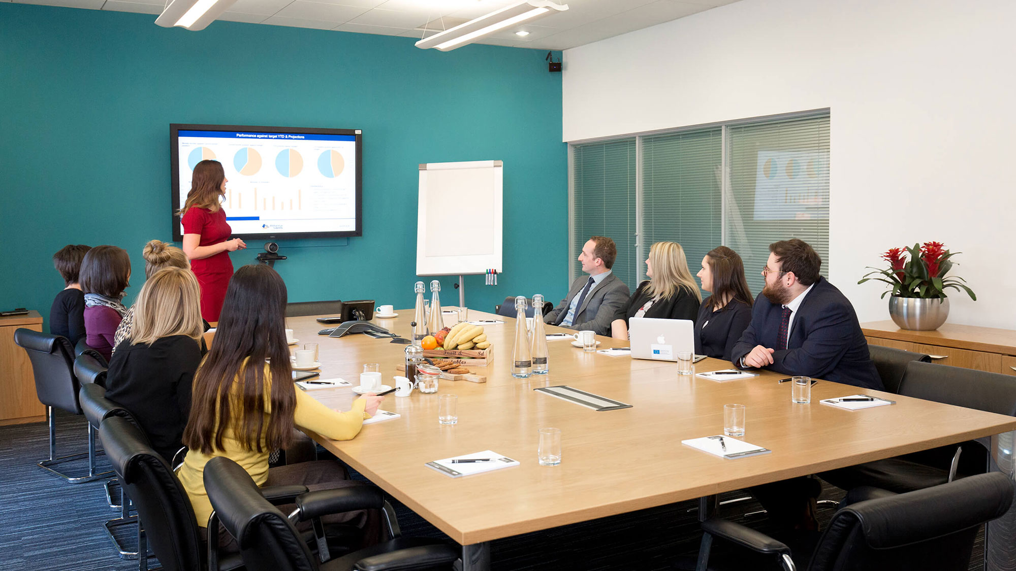 Employee presenting in front of colleagues in a meeting room