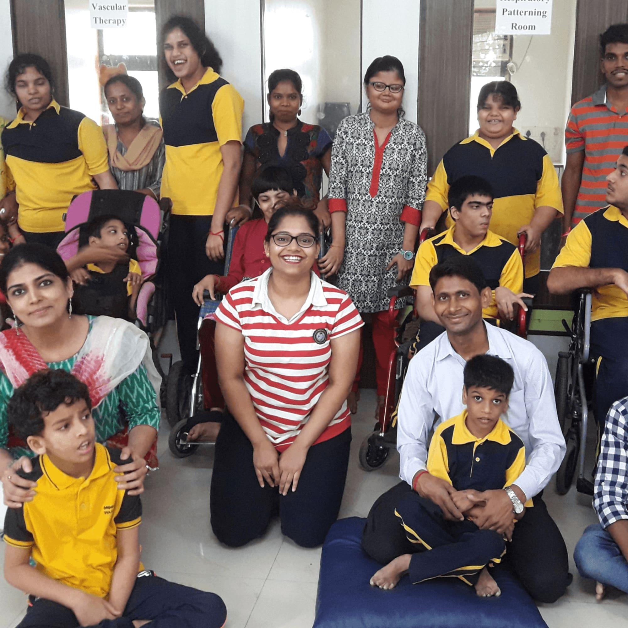Aishwarya Deshpande kneeling on floor amongst students