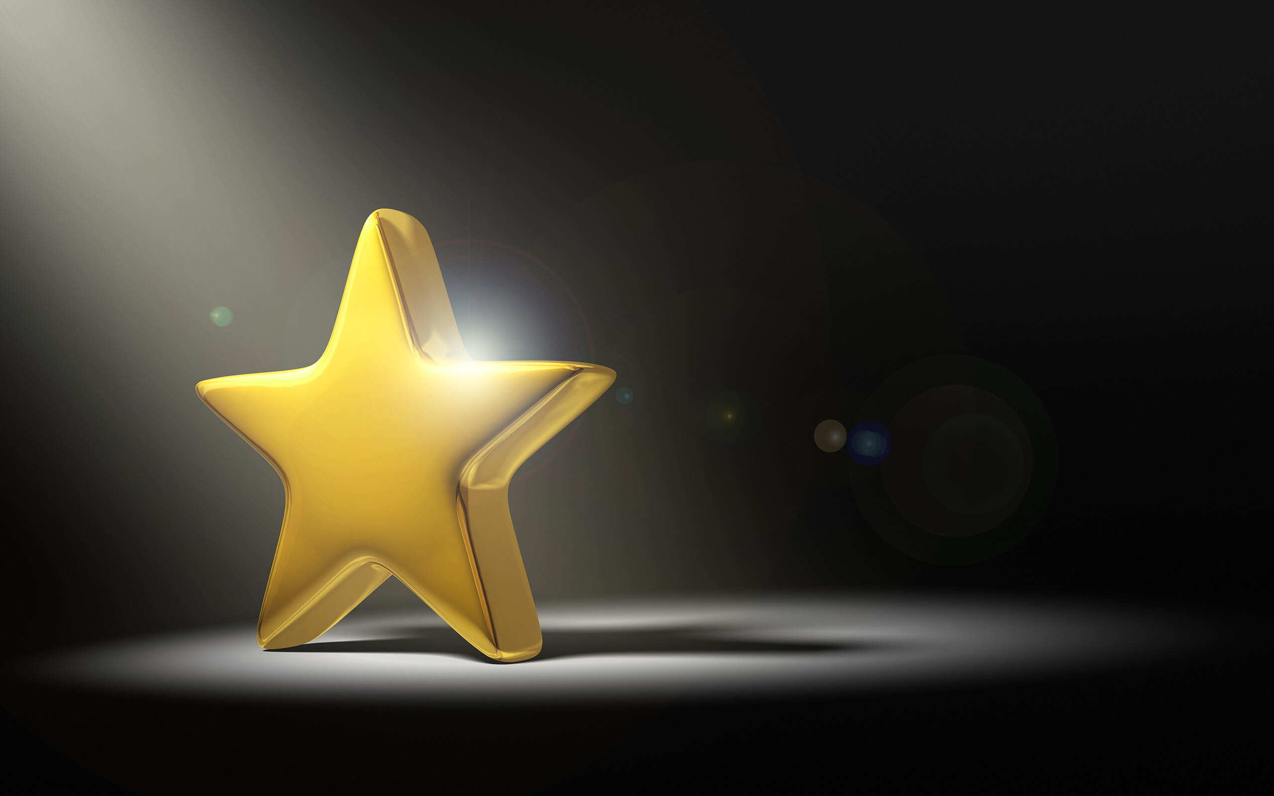 Gold star shining under a spotlight on a black background