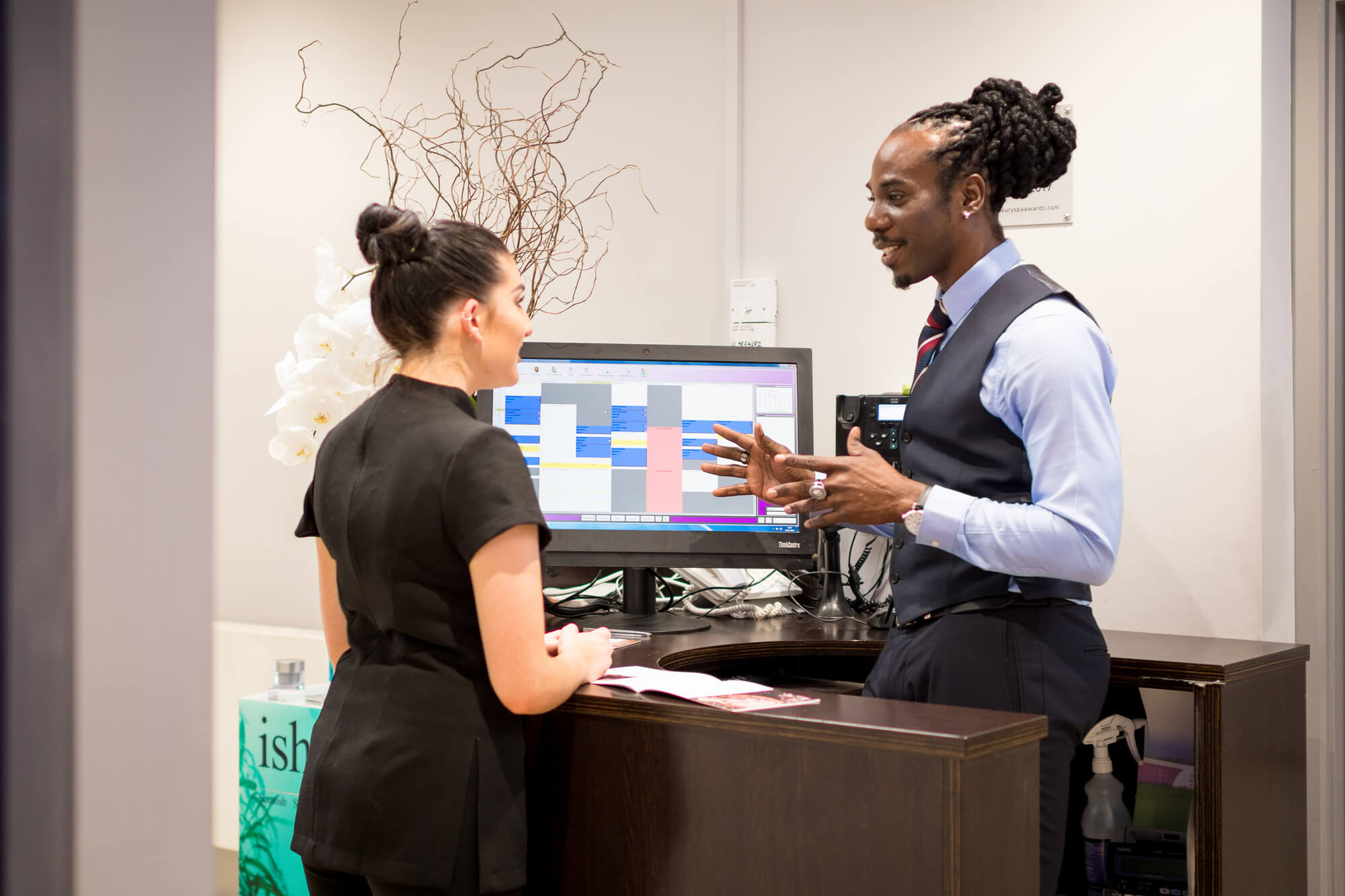 Spa student on work placement talking to spa employee at reception desk