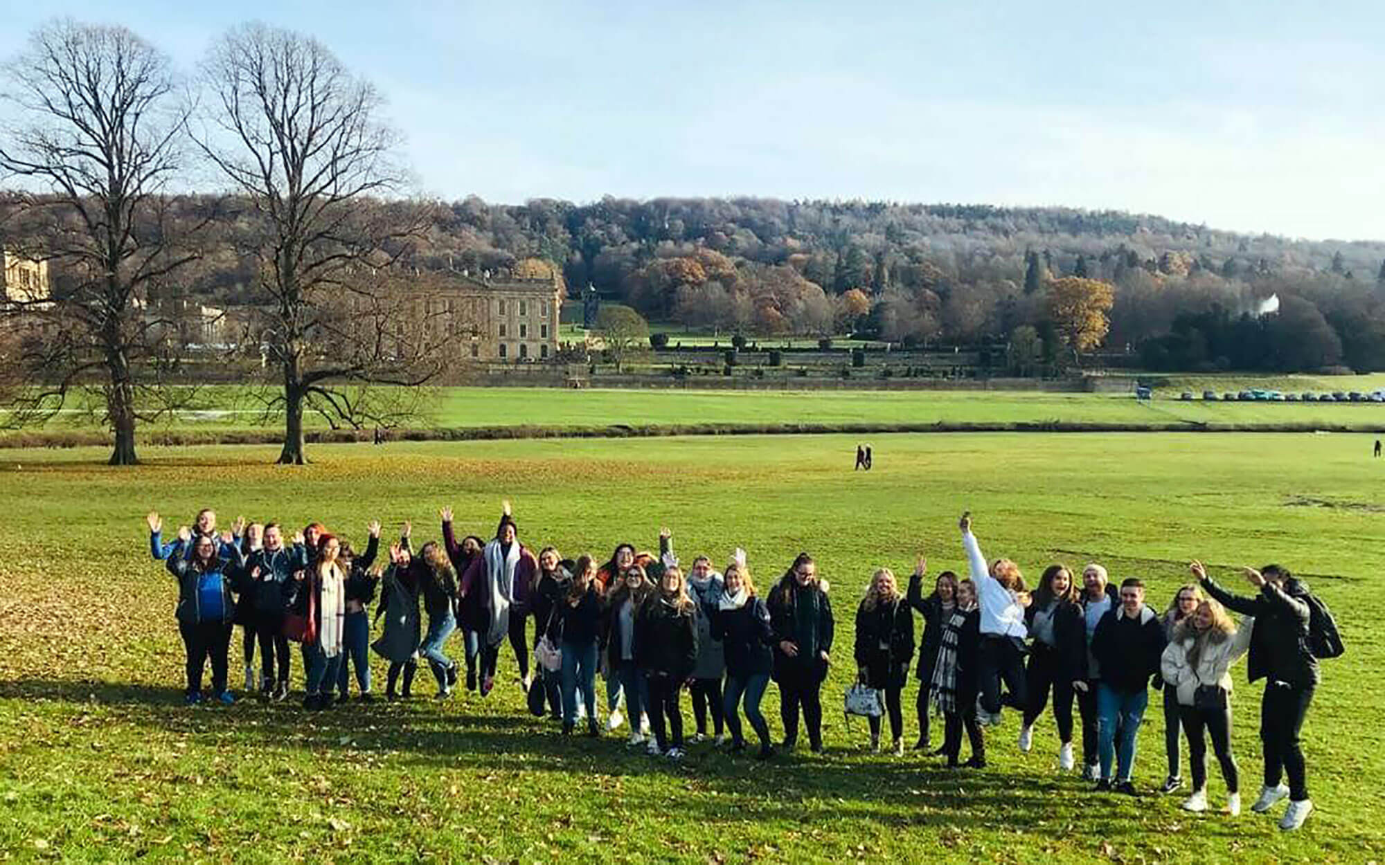 A group of students cheering in a field at Chatsworth