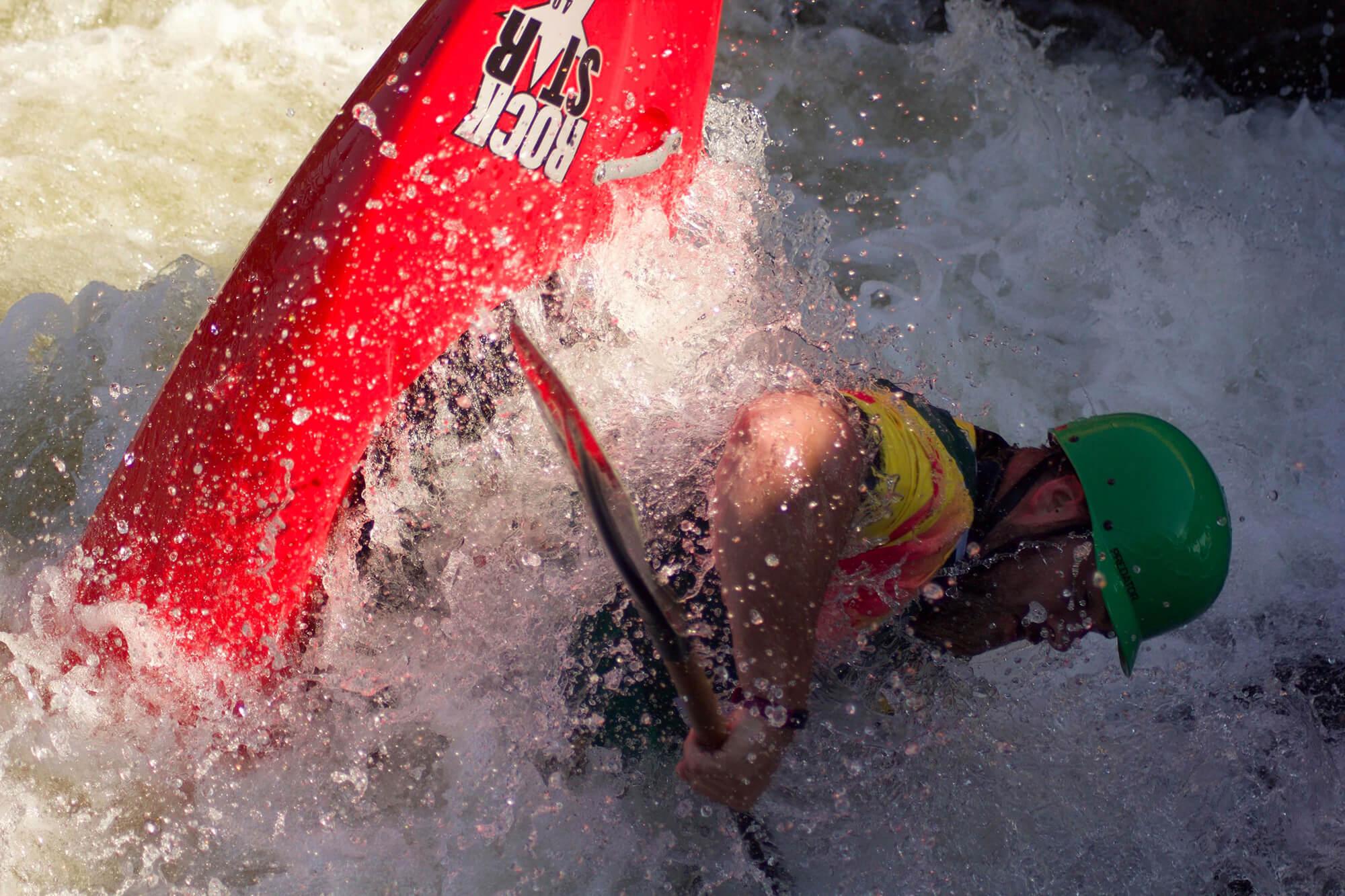 A man kayaking through extreme white water
