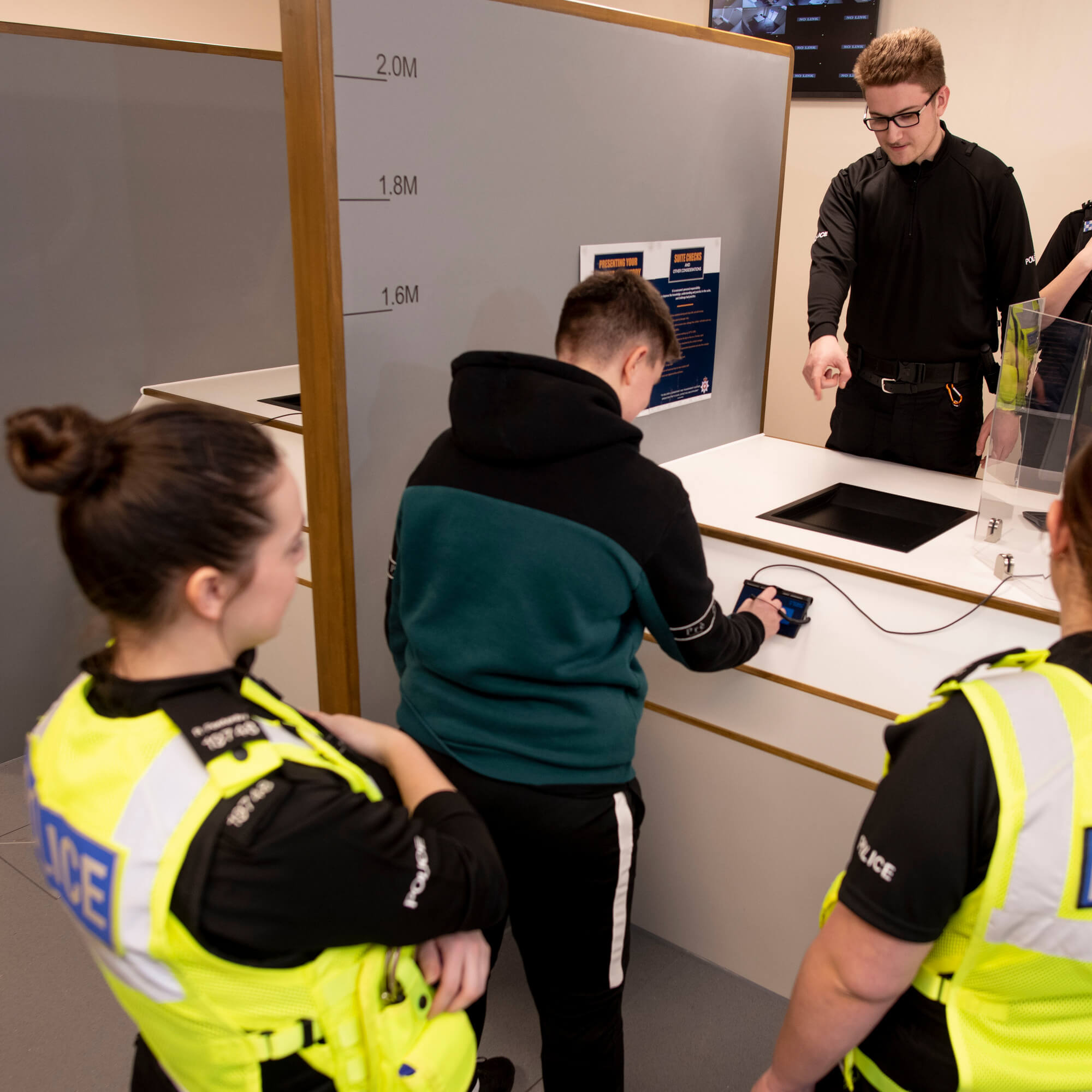 Policing students in uniform booking in a suspect at the custody suite desk