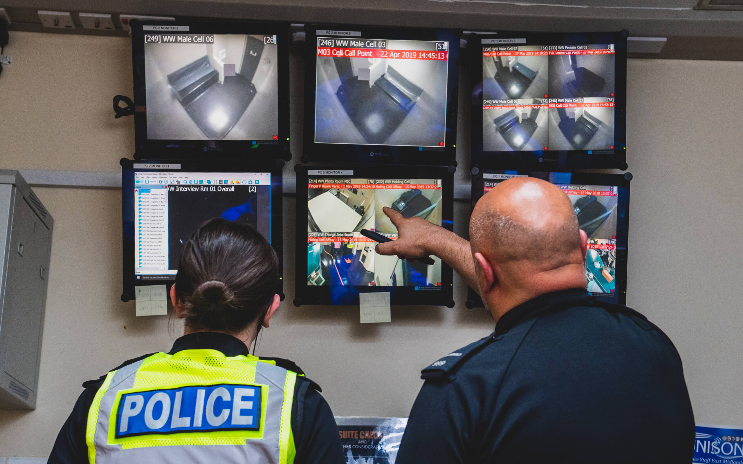 Two police officers looking at CCTV camera feeds