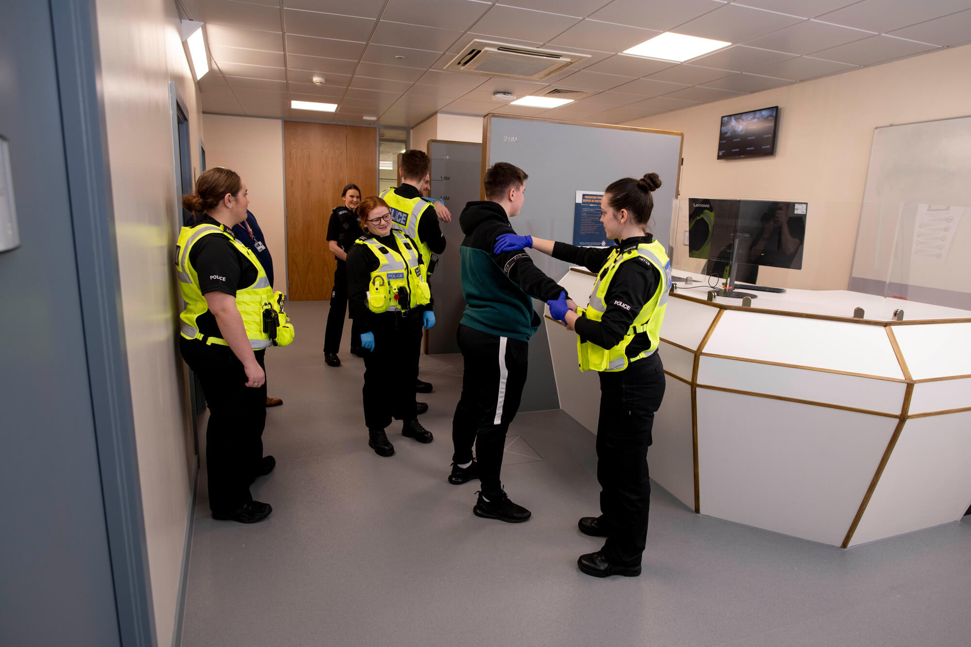 Policing students in uniform performing a search on a suspect at the Custody Suite booking-in desk