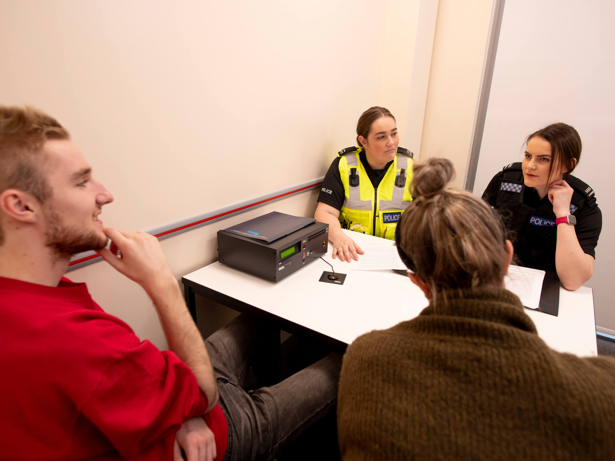 Policing students in uniform in an interview room question a suspect who is sitting beside their legal representative