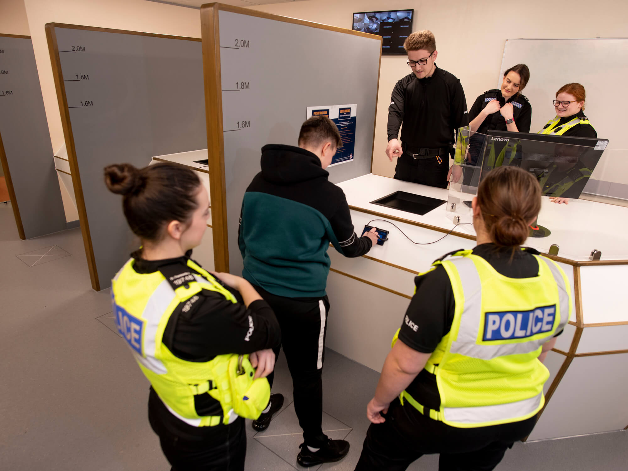 Policing students in uniform learning the booking in process with a suspect signing in at the custody suite desk