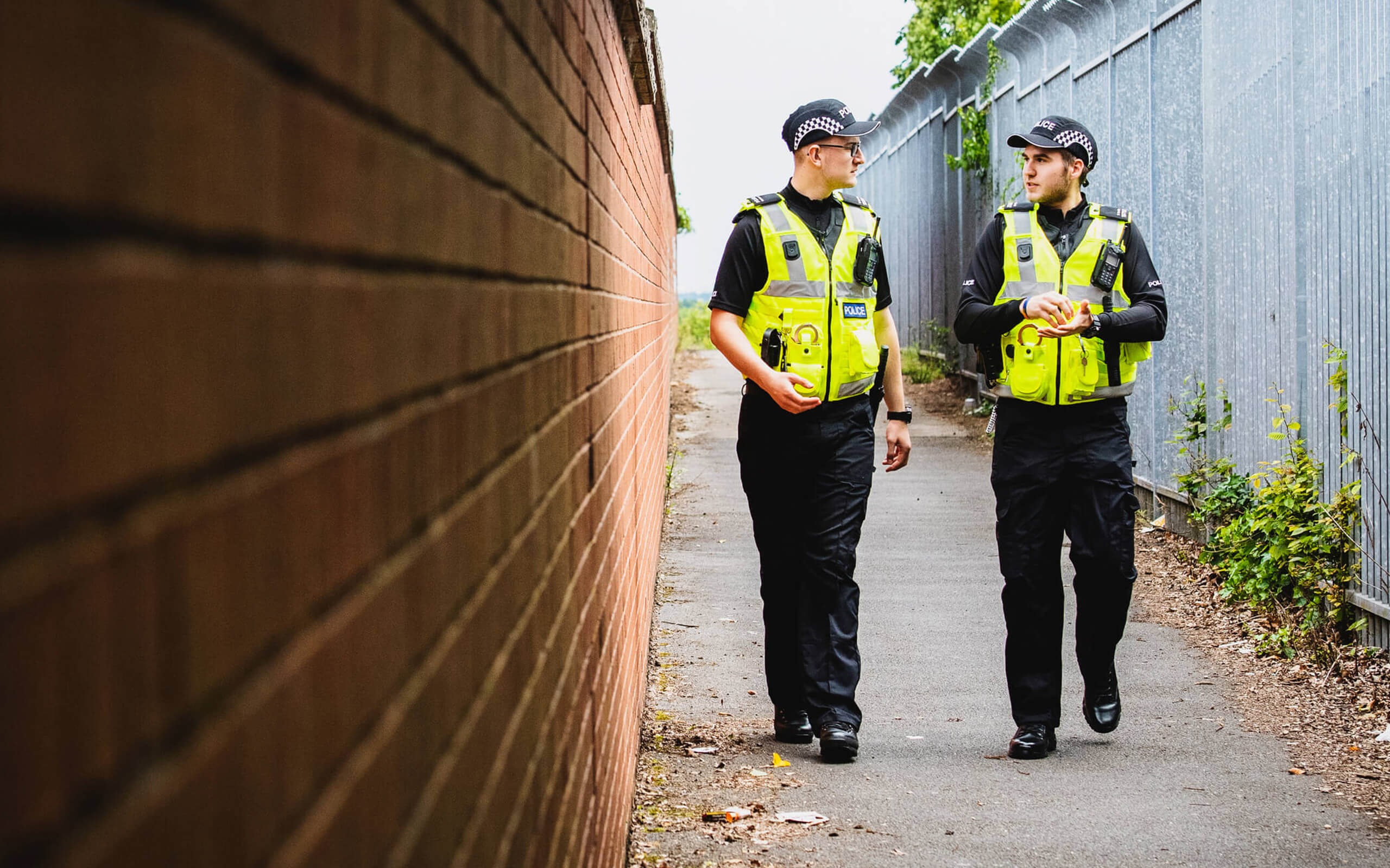 Two policing students walking down an ally way talking
