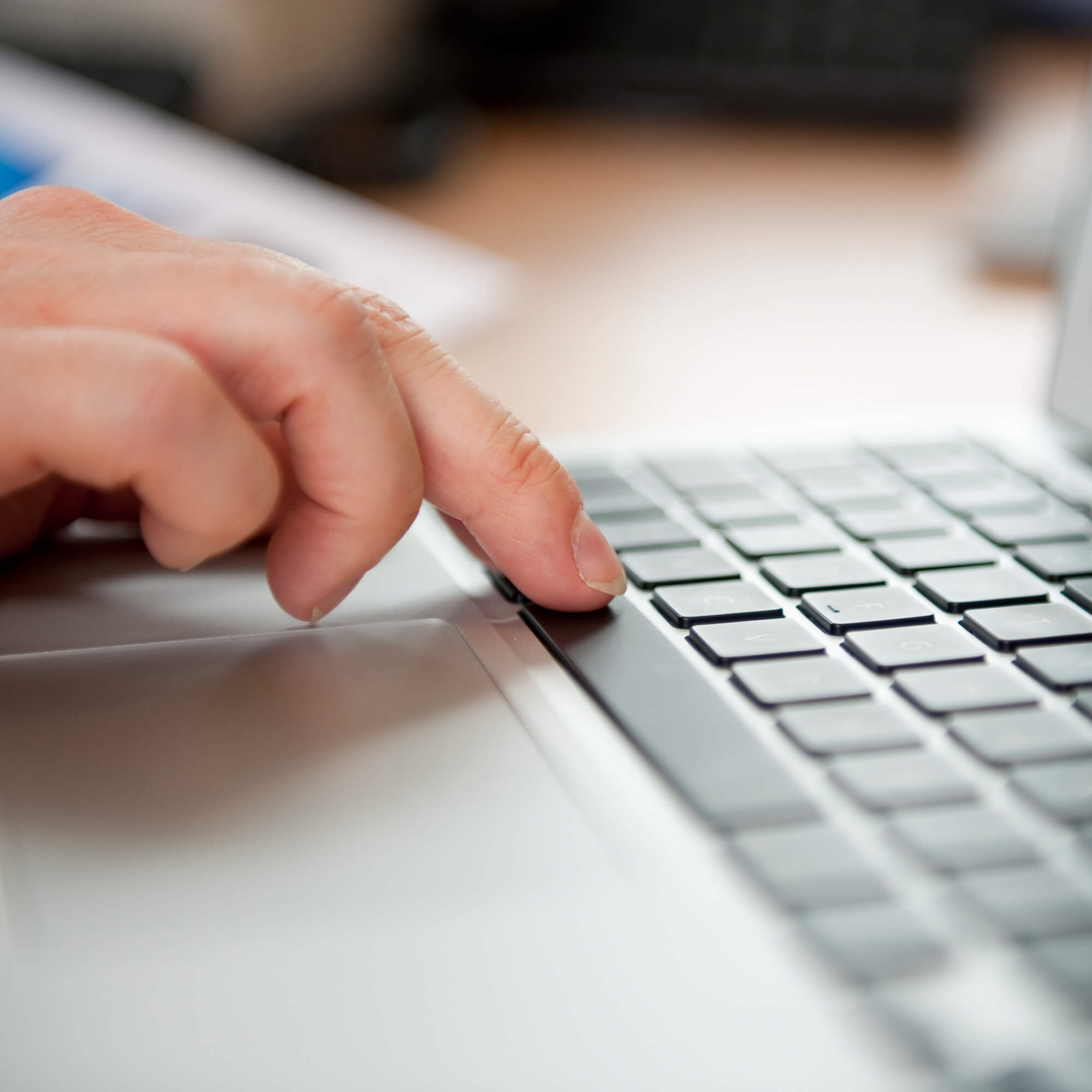 A close up of a hand on a laptop keyboard