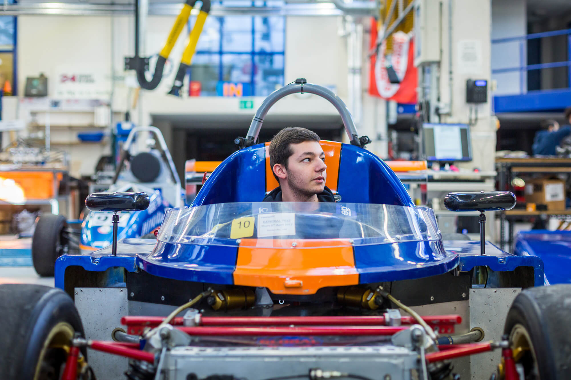 A student sat in the student car in the motorsport workshop