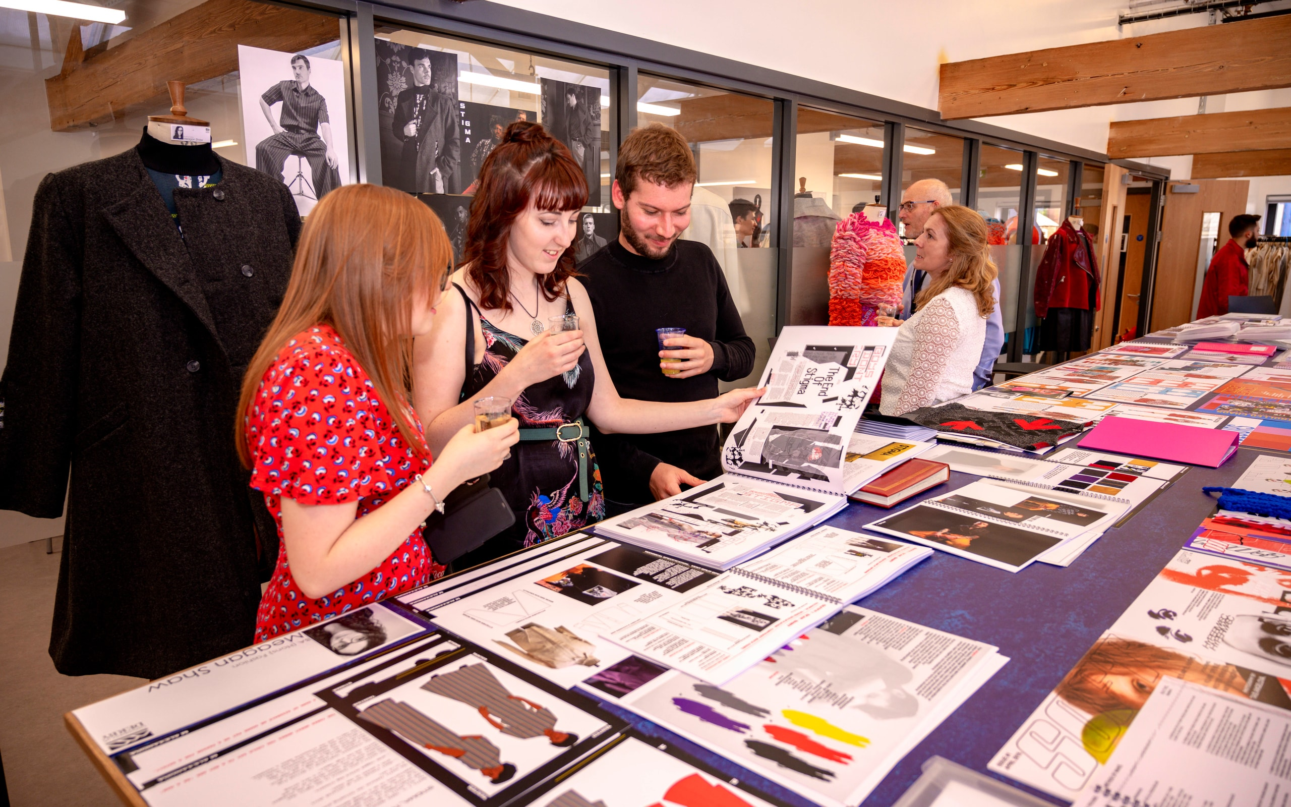 Visitors looking through degree show art student portfolios