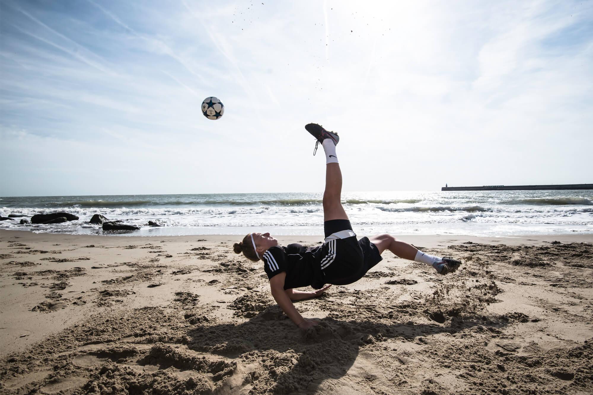 Football Journalism Student Playing Football on Beach
