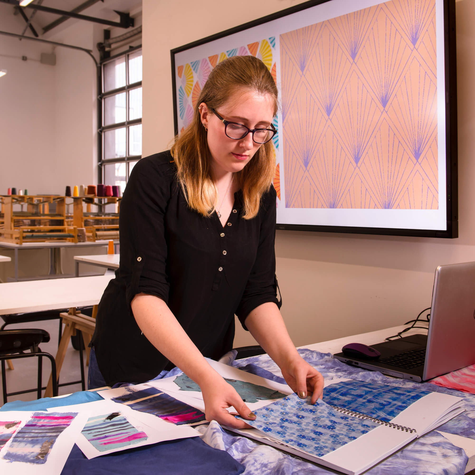 MA Fashion and Textiles student arranging textiles work
