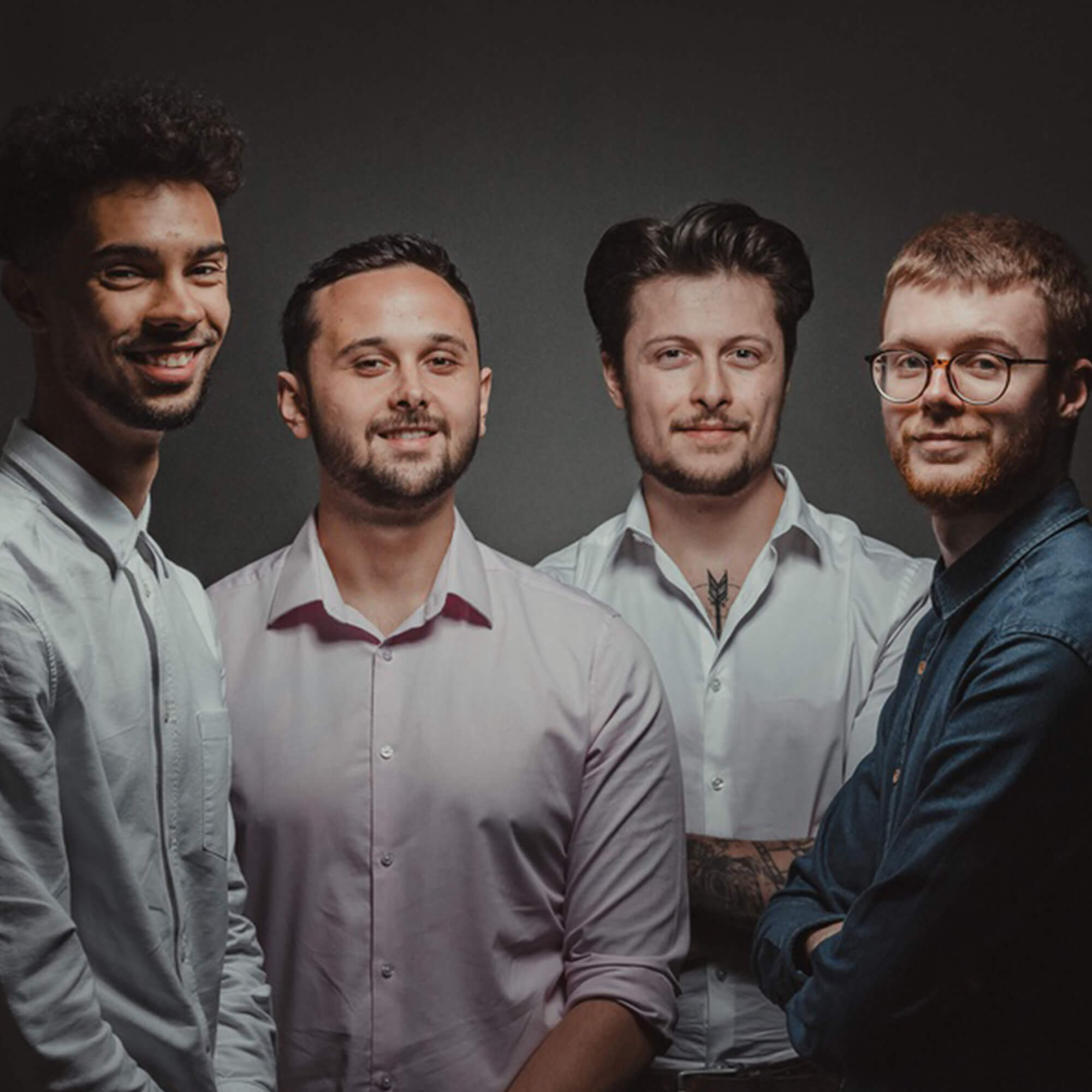 Goldbox film production team consists of four men. In this image they stand together against a black background, they are wearing shirts and smiling.