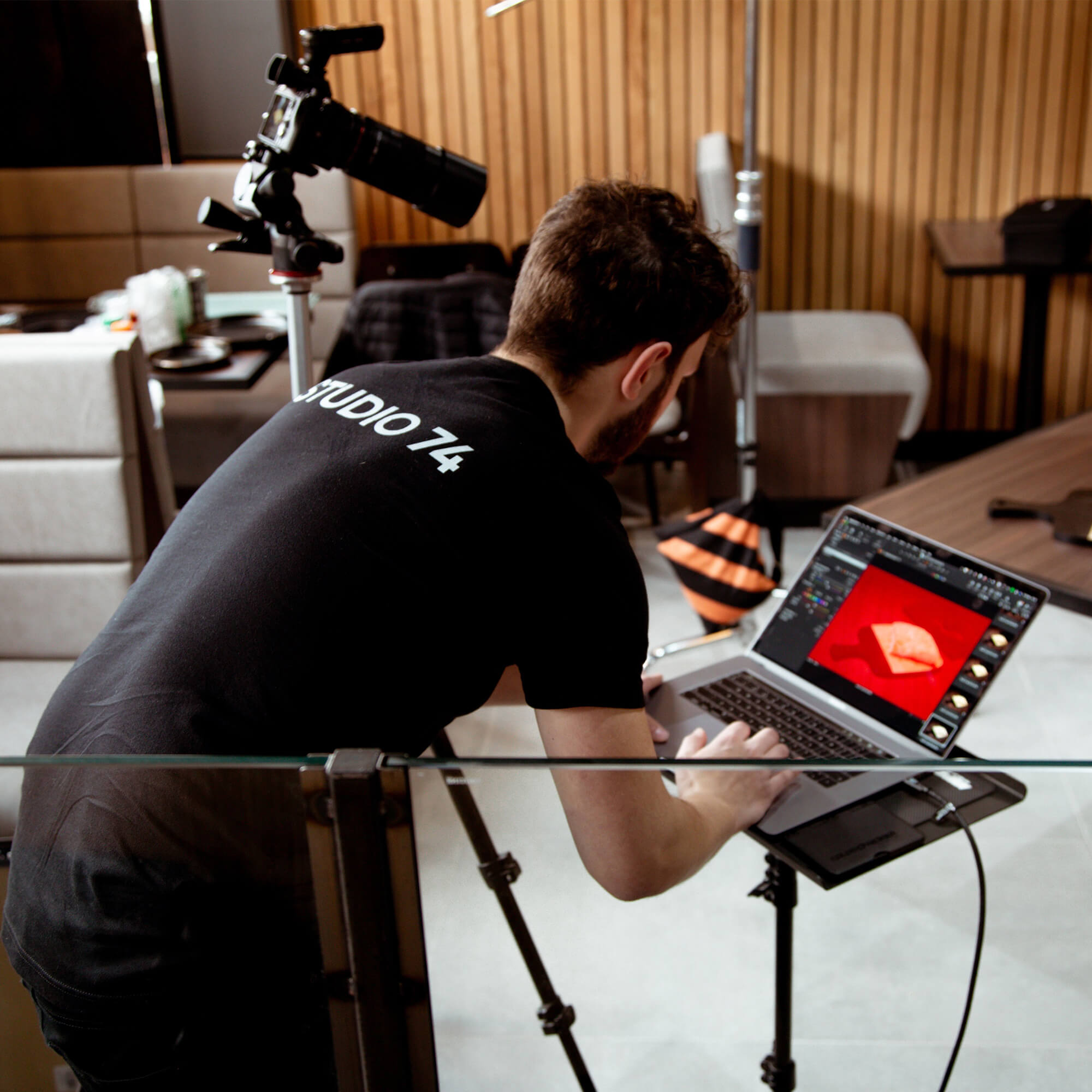 Dariusz working on a laptop in a photography studio.