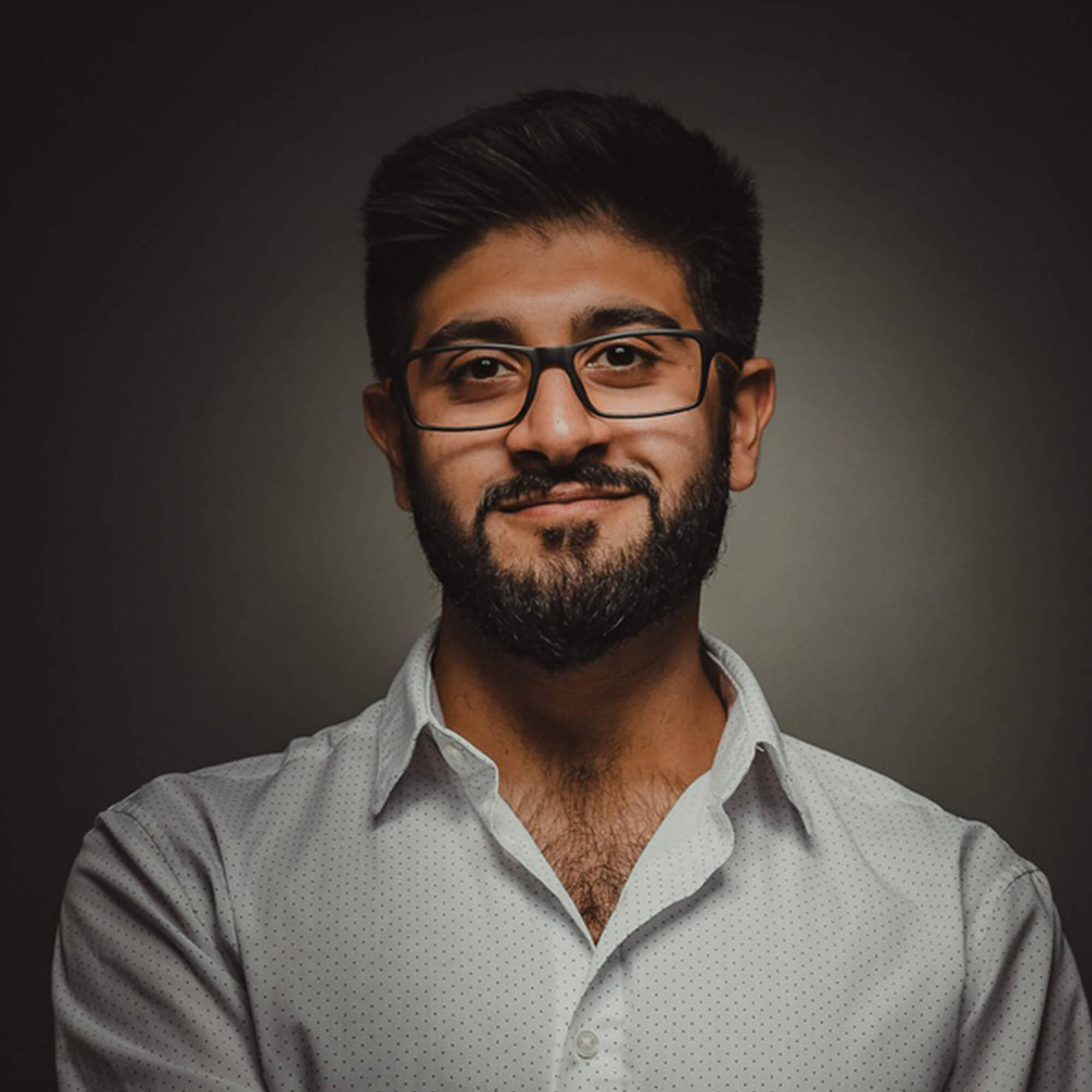 Omar wearing a white shirt and glasses.