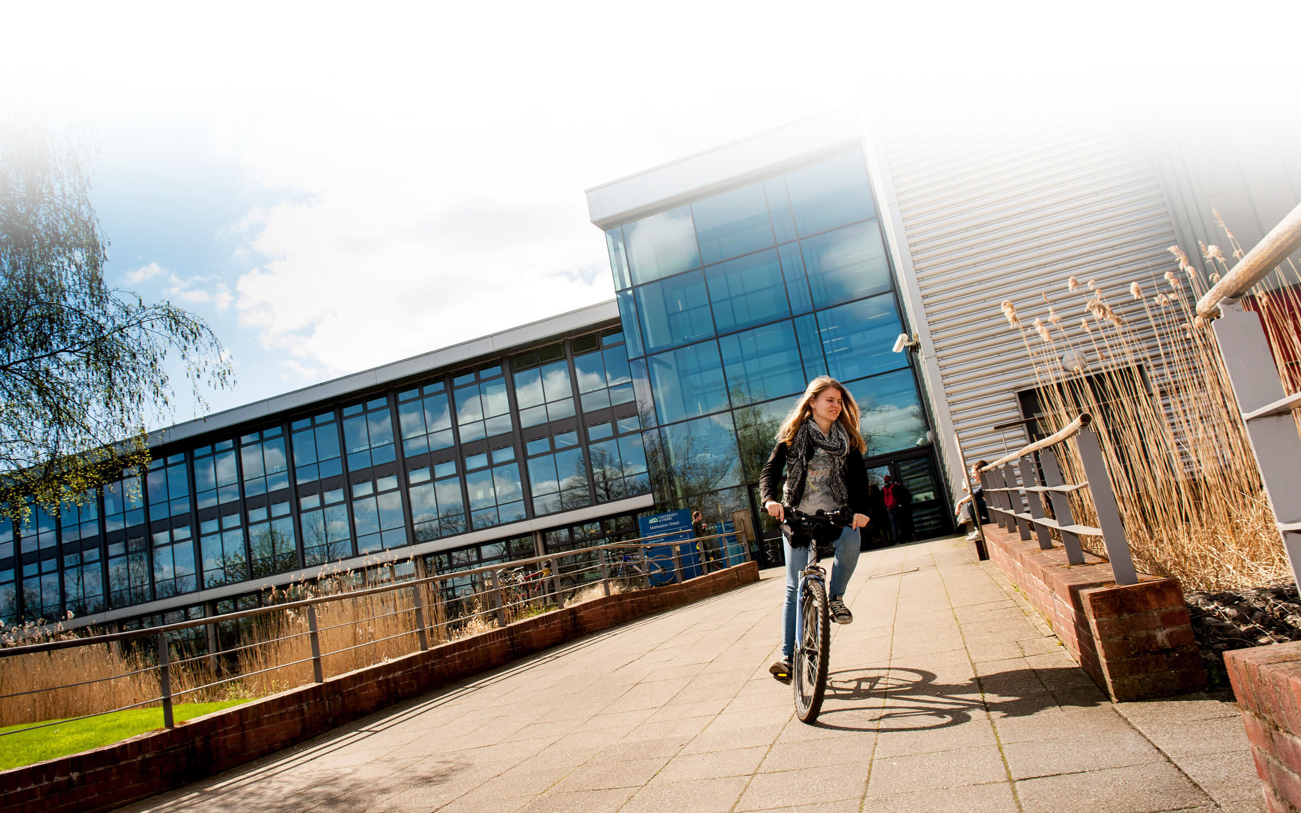 A female student riding a bike at Kedleston Road