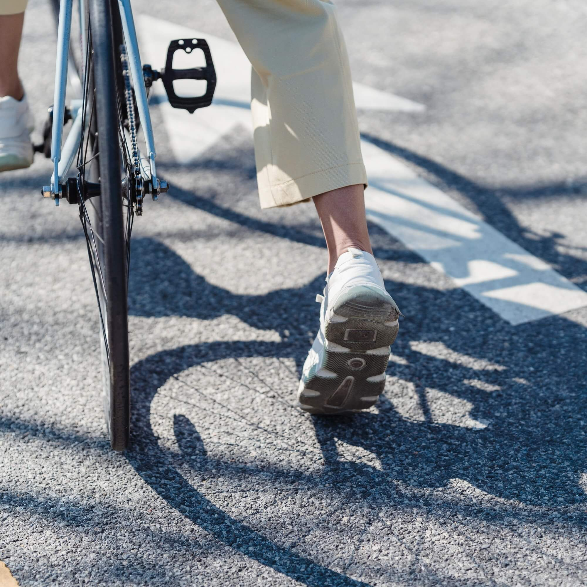Person setting off on a bike, wearing white trainers, shadow of the bicycle wheel on the road.