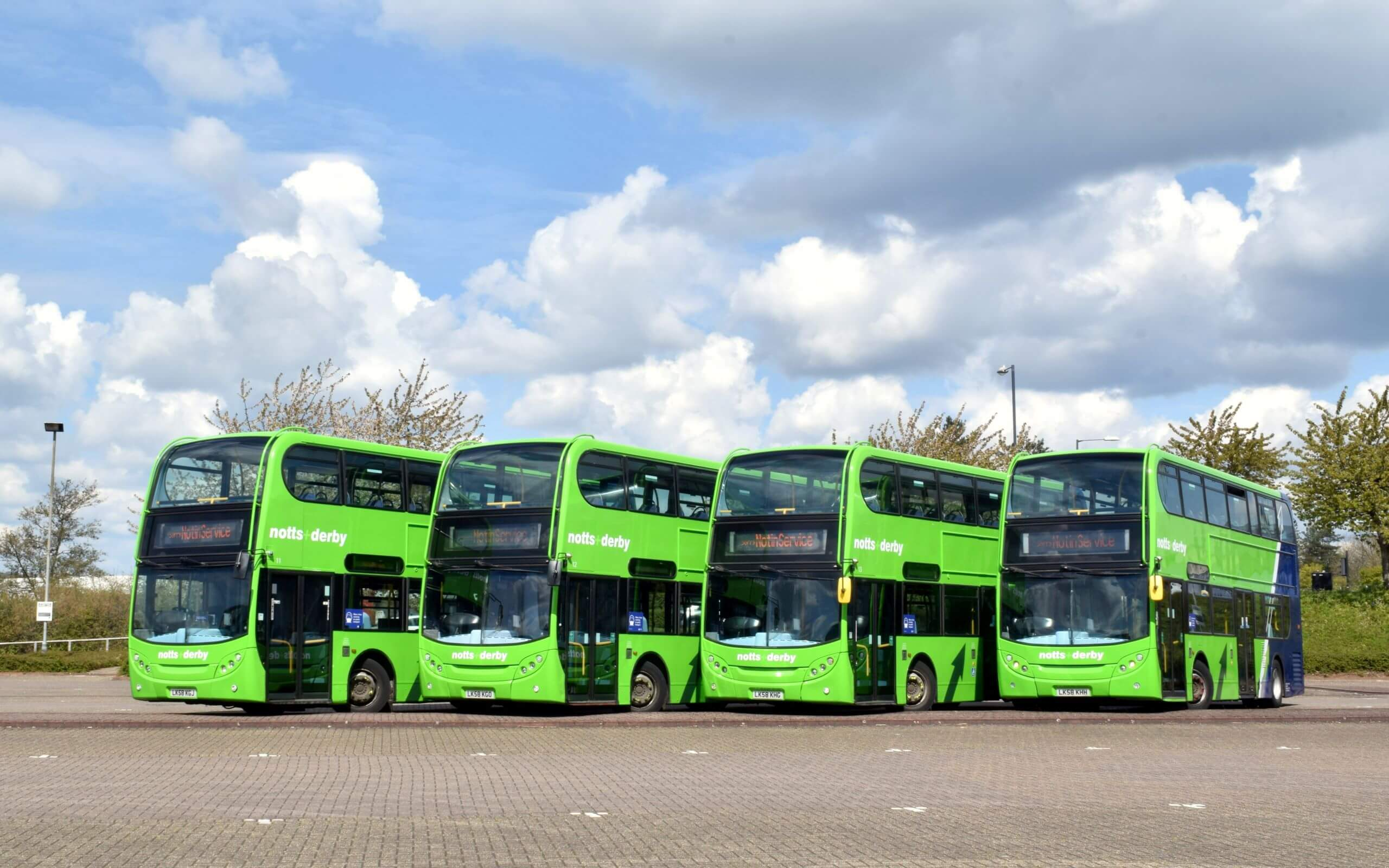 Four green double-decker buses