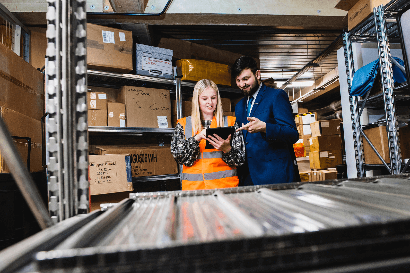 Two people are checking stock in a logistics warehouse