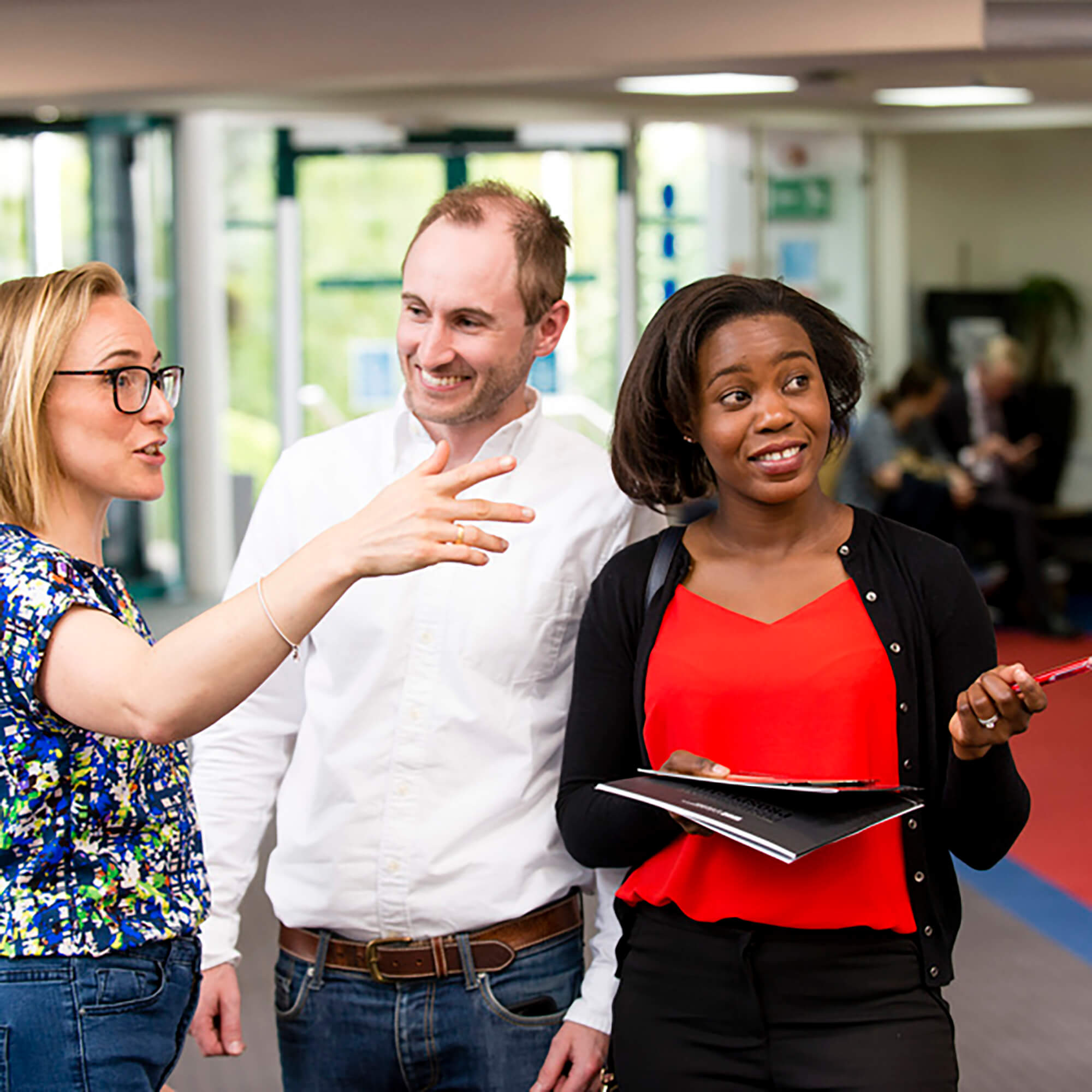 University employee talking to two guests at an Open Day whilst pointing to the direction they need to go