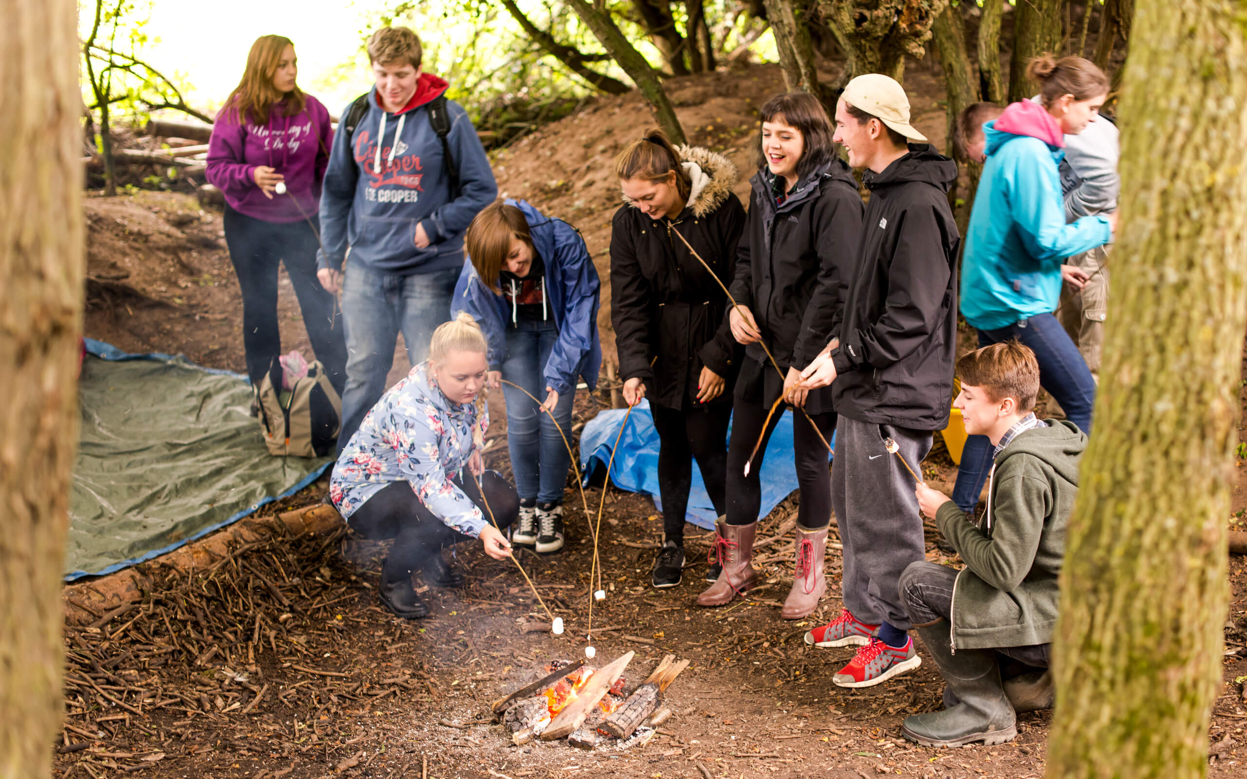 Group of young people in the woods around a fire