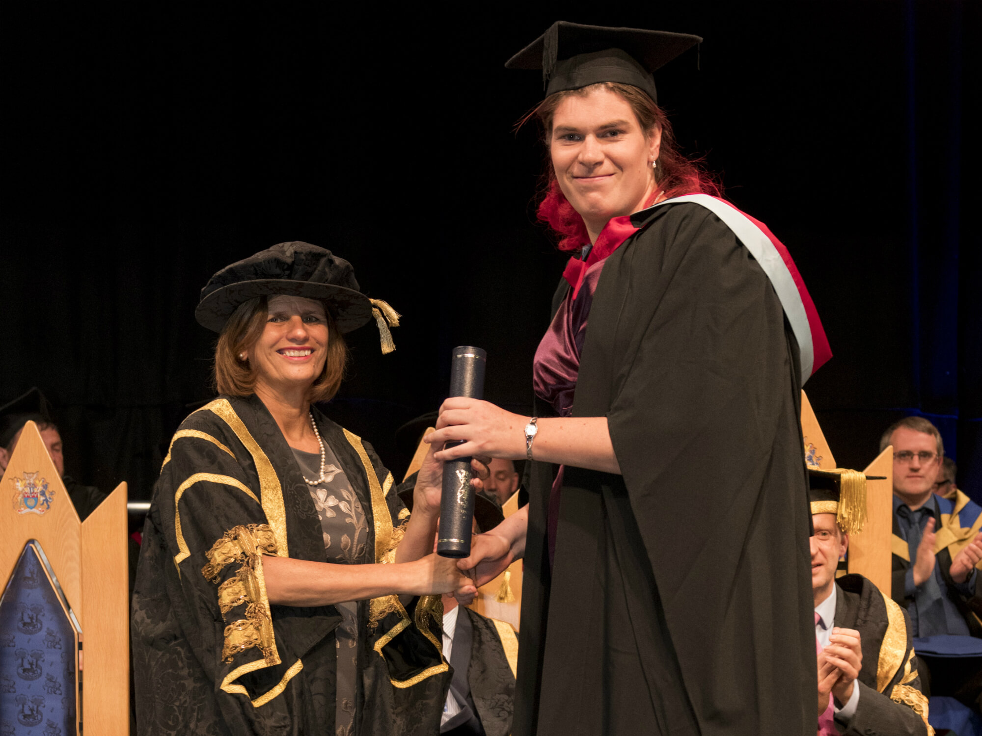 Young woman in a graduation gown, receiving the award from female Vice-Chancellor