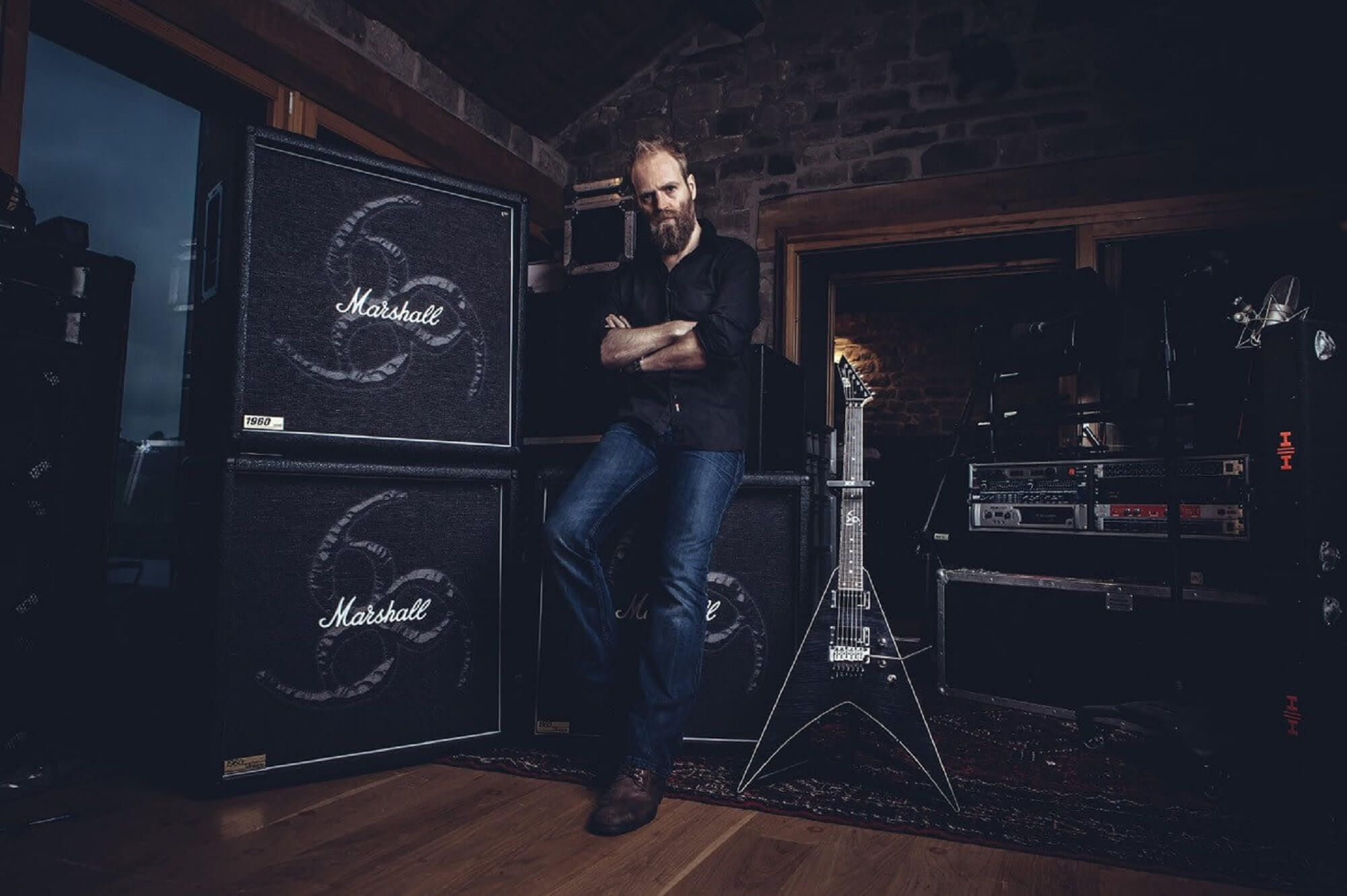 Rock producer Andy Sneap pictured in a recording studio with guitars and amplifiers