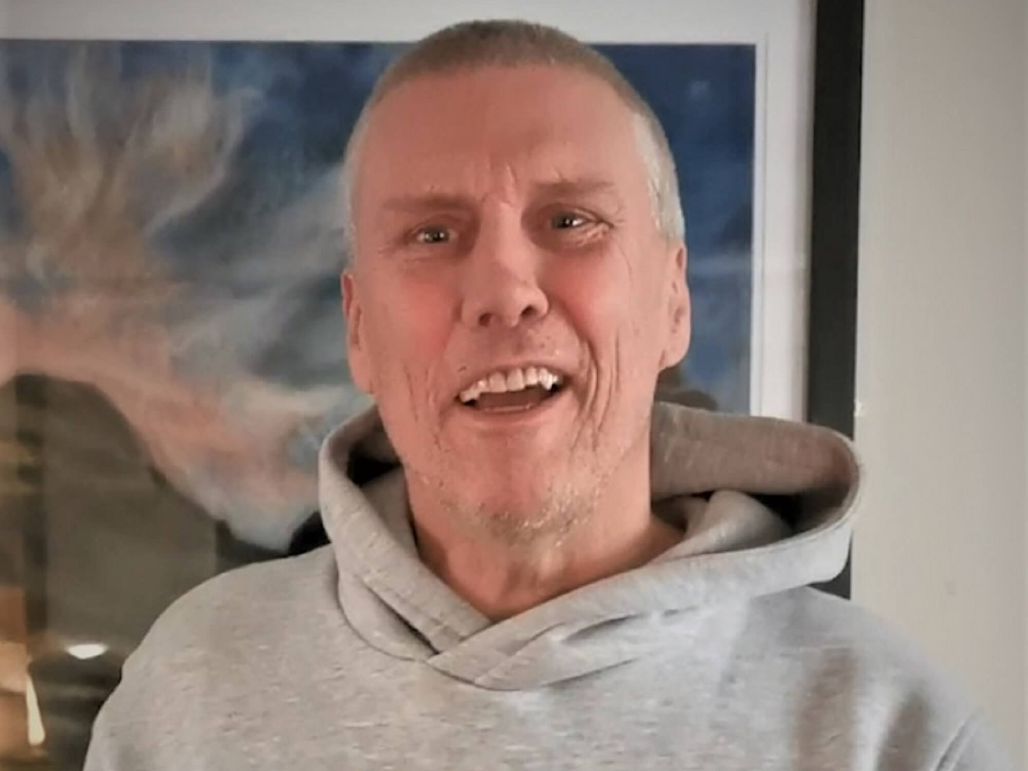 Portrait of Bez in front of a picture
