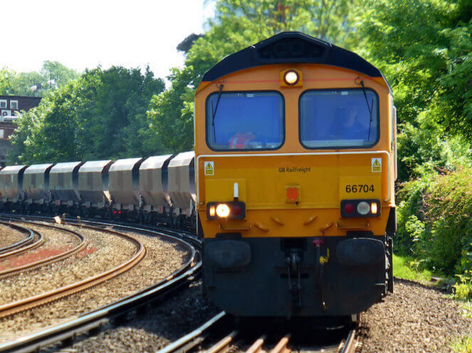 Freight train engine with wagons travelling on tracks in the UK