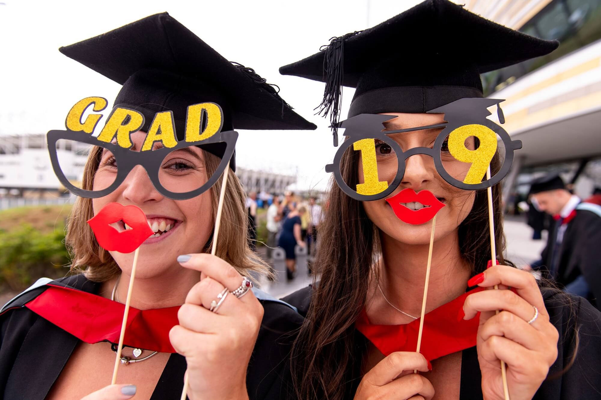 Two students at graduation holding comedy glasses and lips saying Grad 19