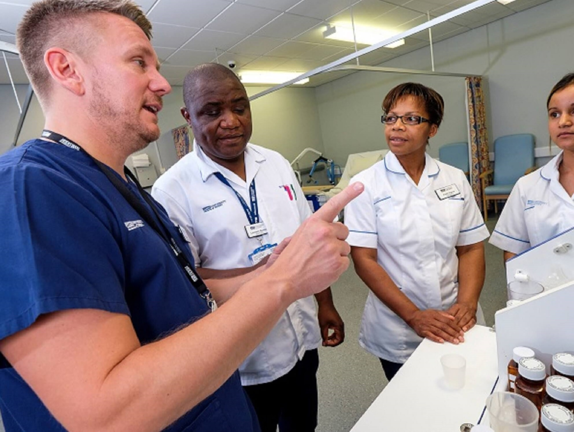 Nursing students receiving tuition in a ward from a senior healthcare staff member