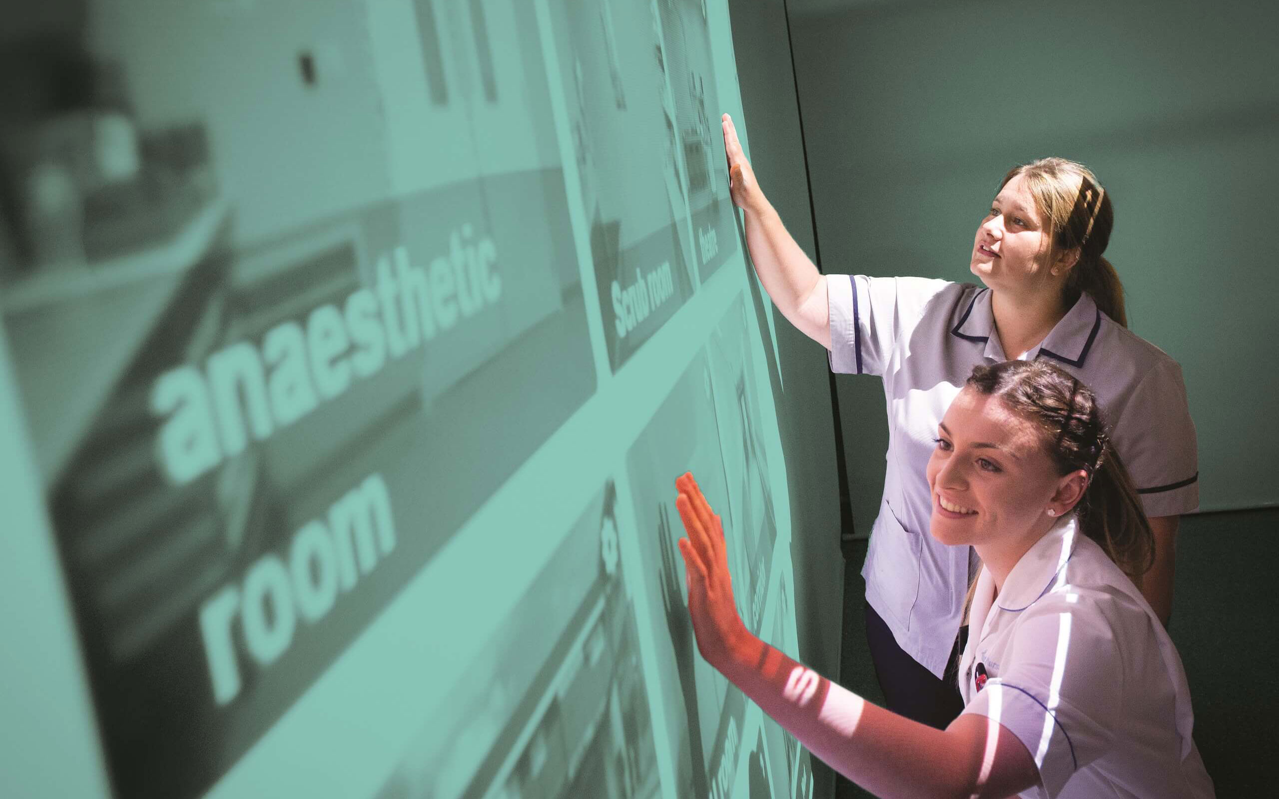 Two nurses looking at an interactive board