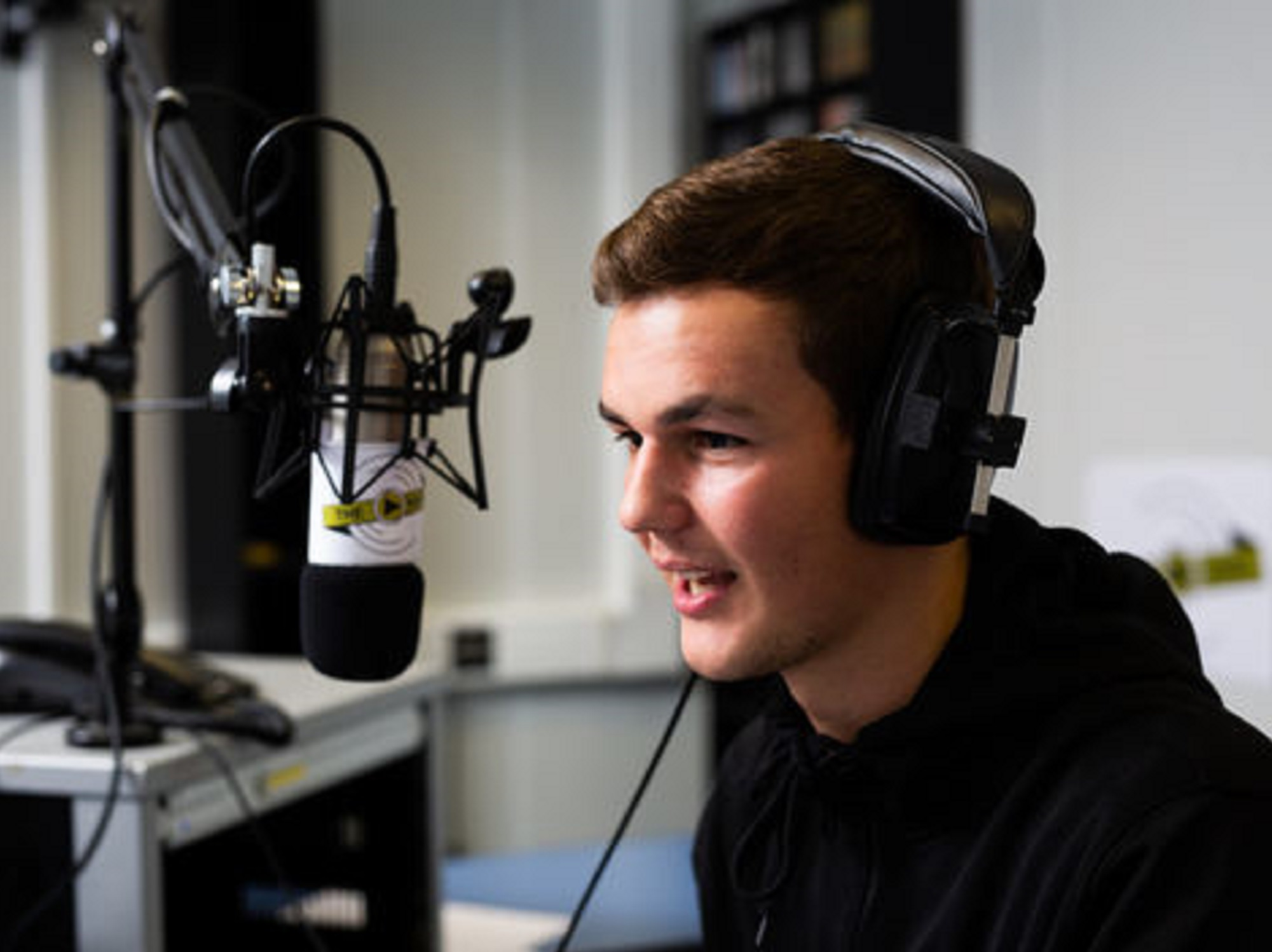 A University of Derby journalism student using a microphone