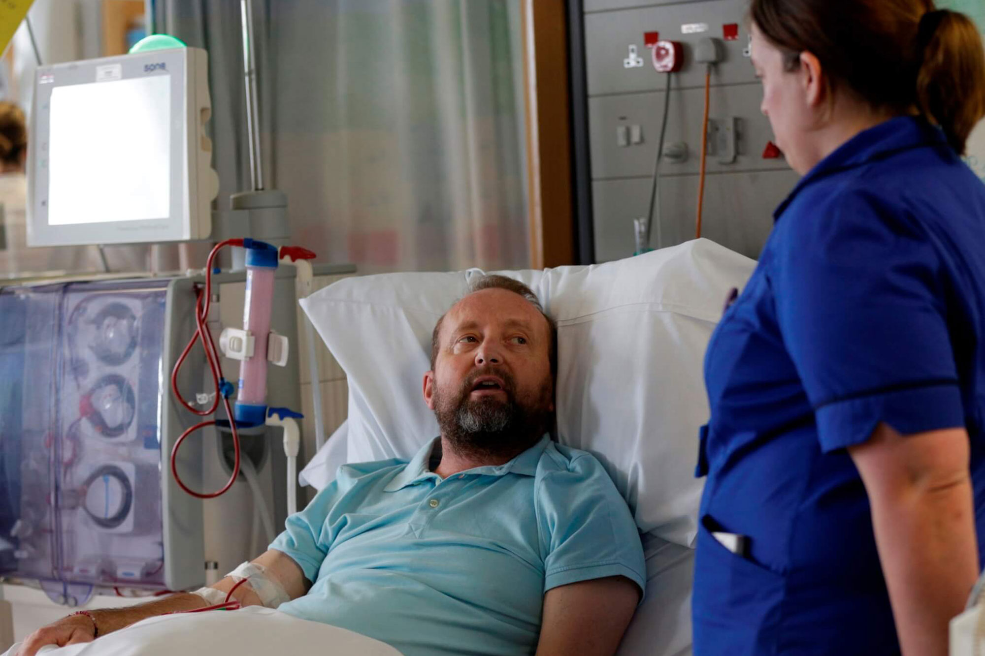 Picture of nurse talking to patient receiving dialysis treatment