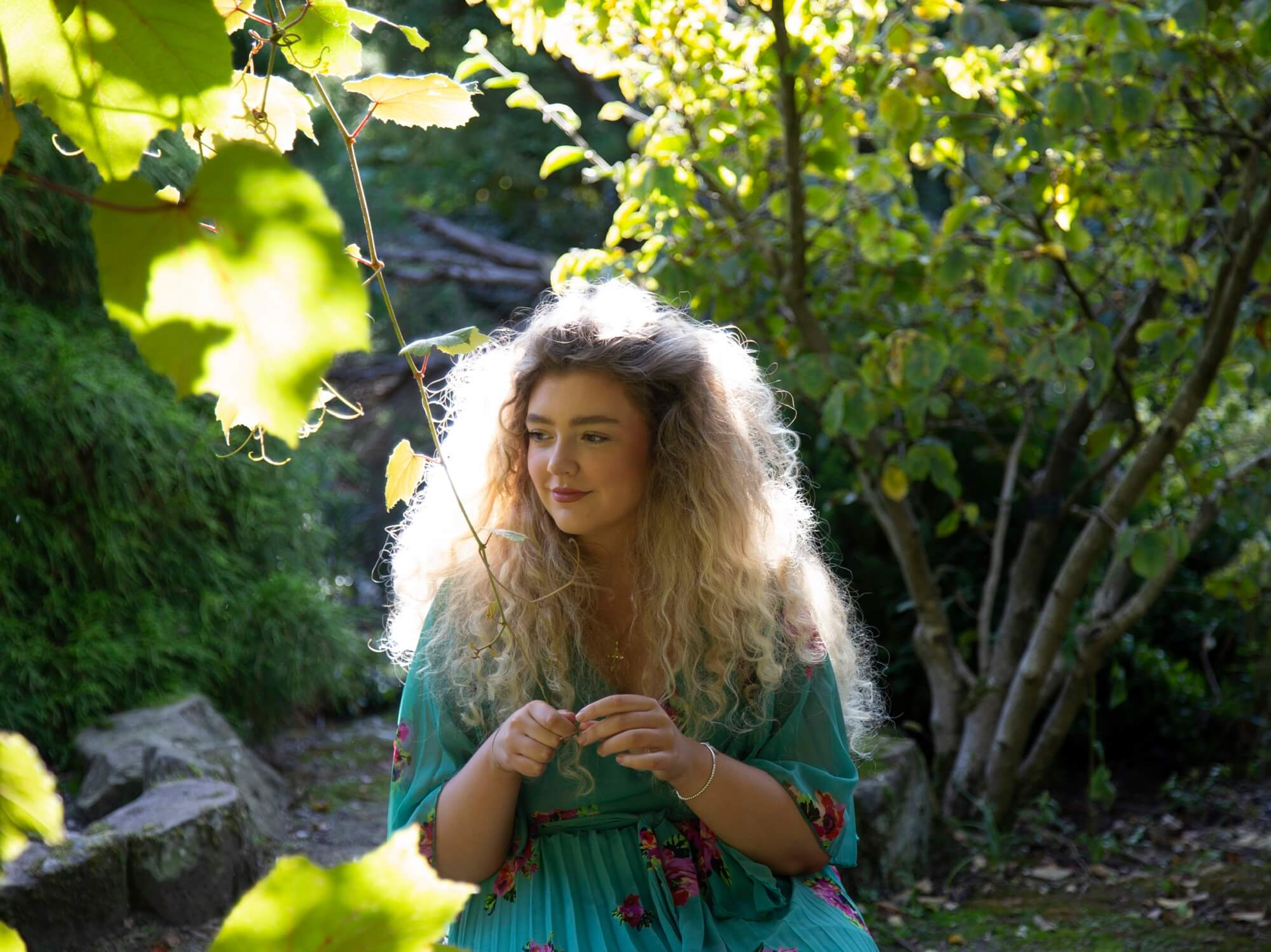 Singer and songwriter LYDIAH sitting in a woodland