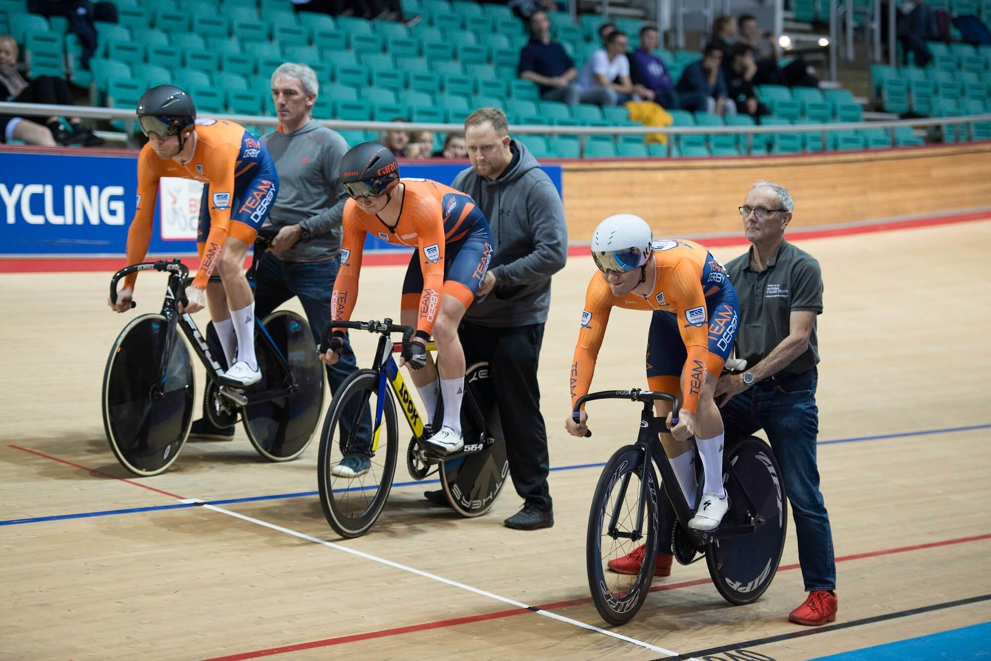Three track cyclists at start line of race