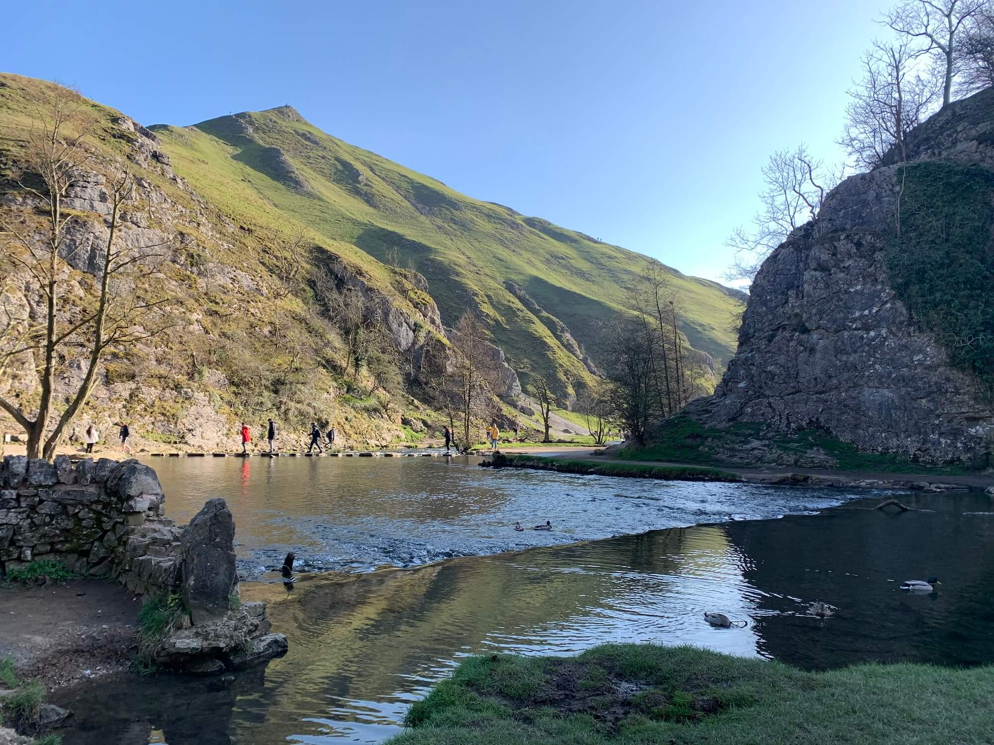 View of people walking over stepping stones at Dovedale