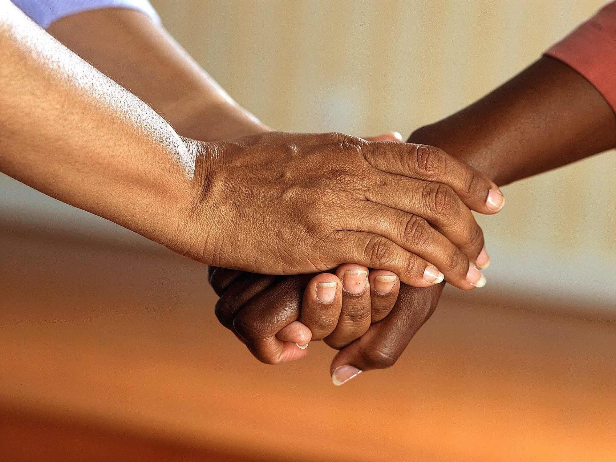 Two people clasping hands to support one another.