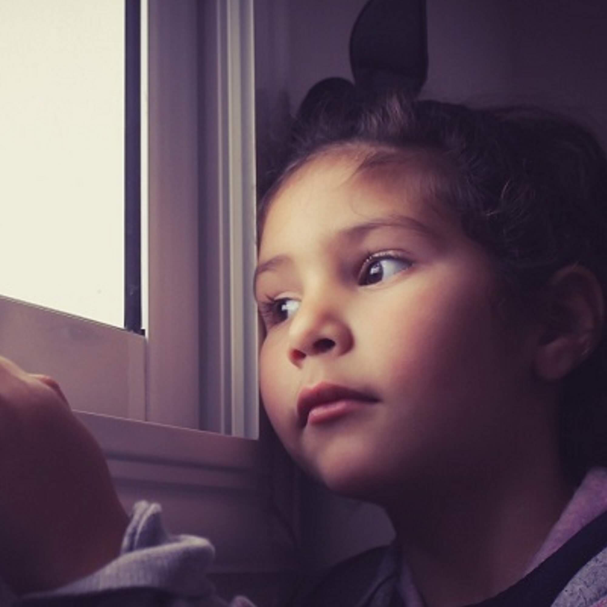 Little girl looking out of a window, worried.