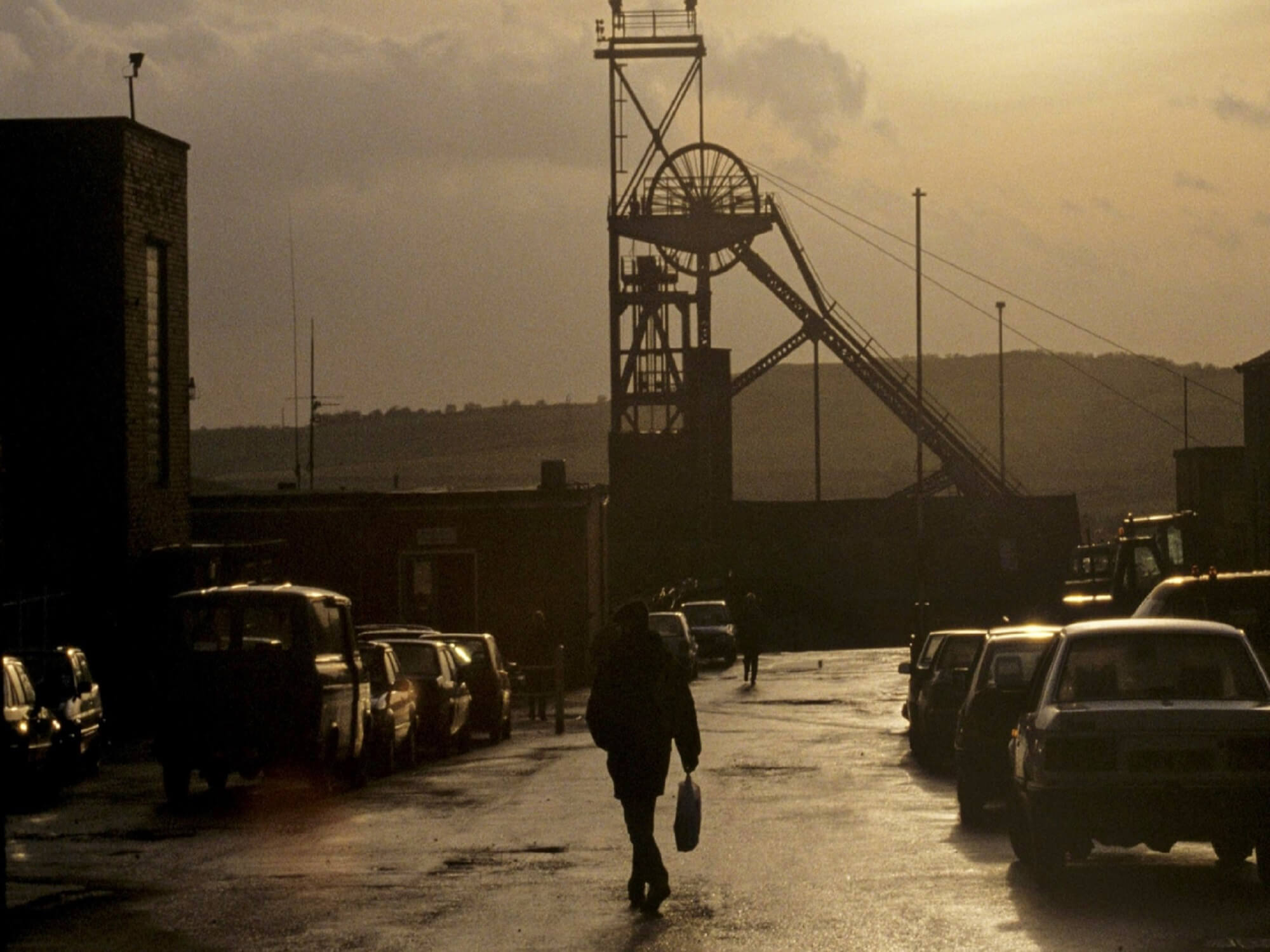 Picture of a pit wheel at a colliery with man walking along the street.