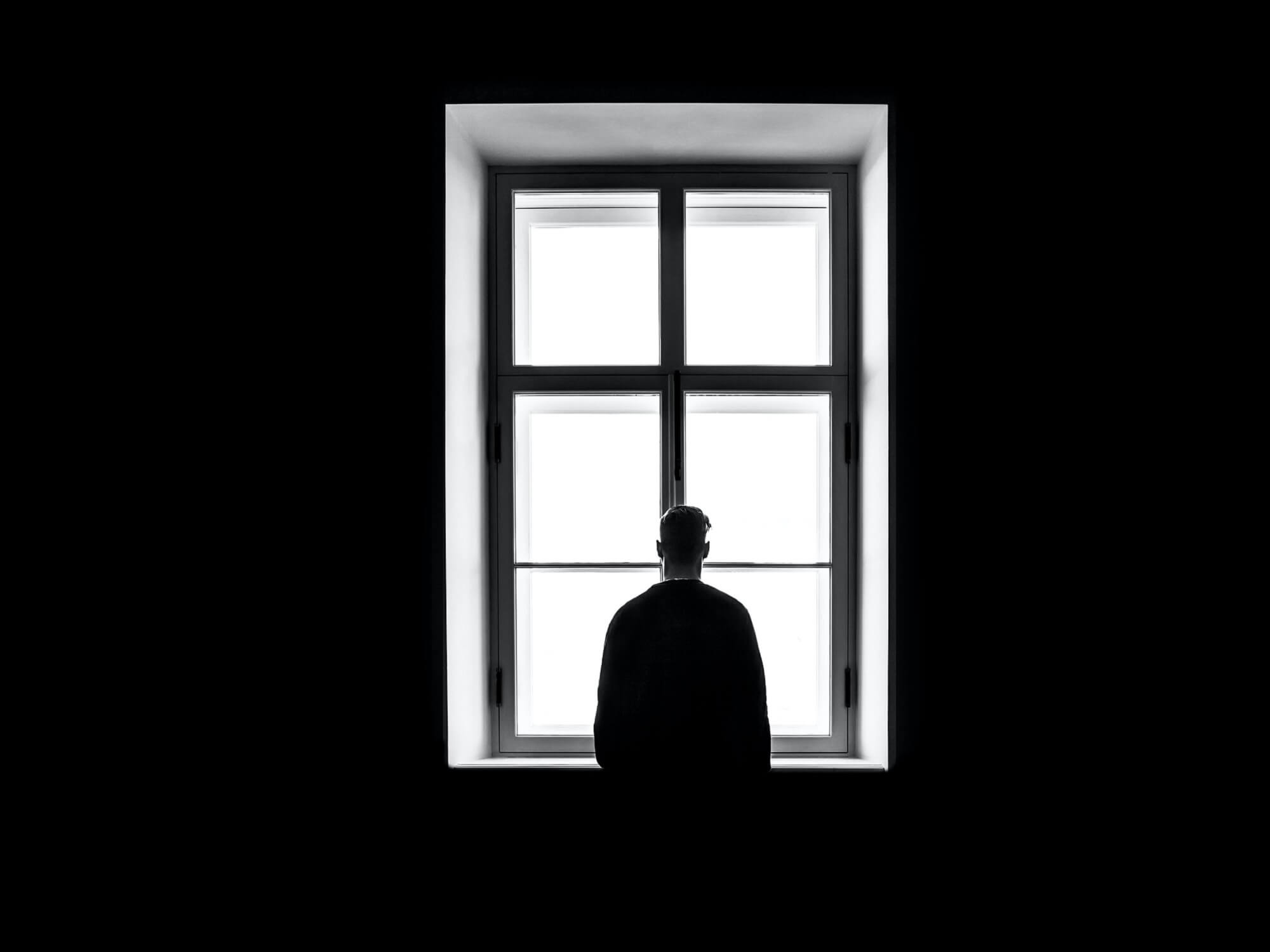 Silhouette of a man staring out of a window