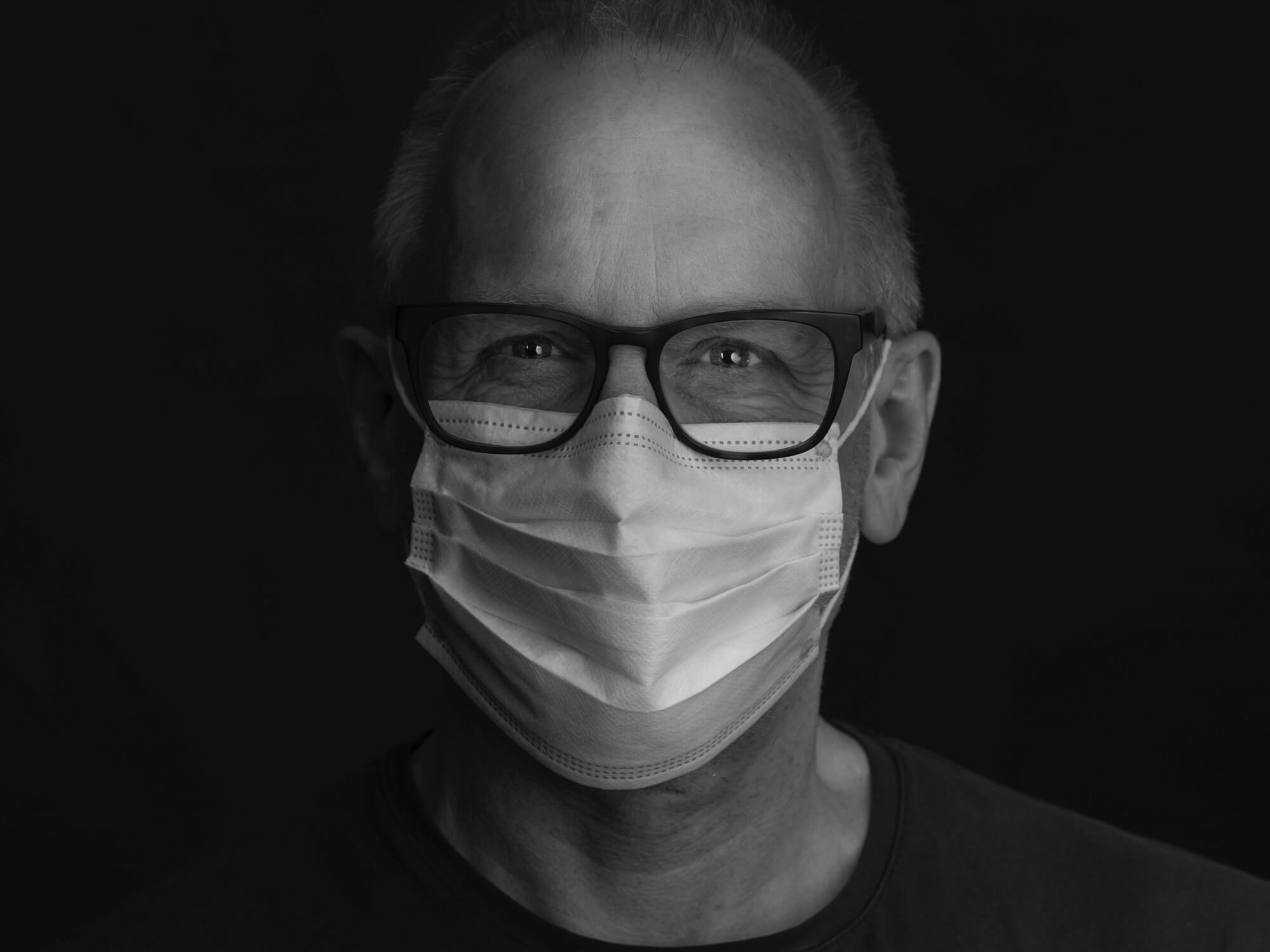 Black and white image of a man with glasses wearing a facemask