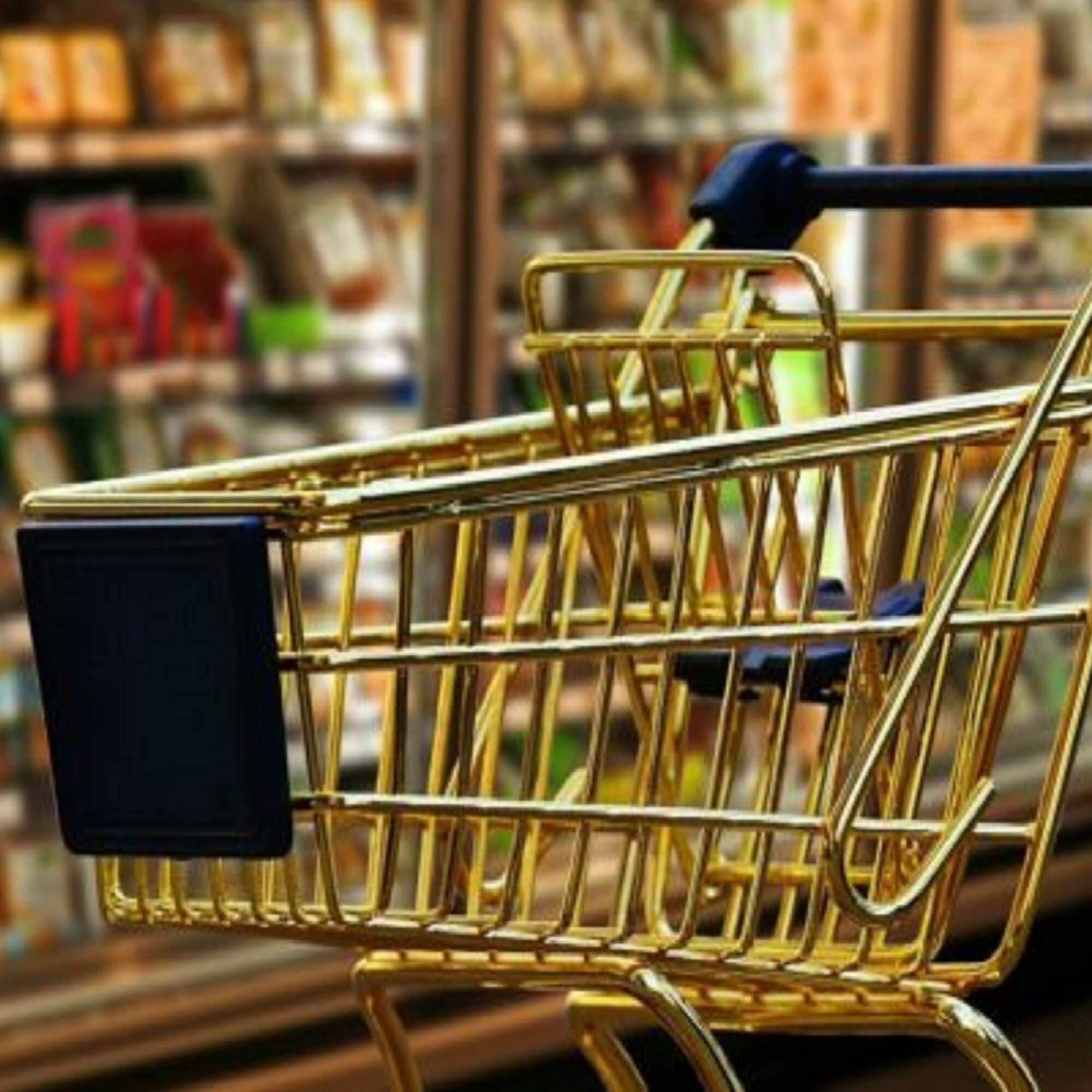Shopping trolley in supermarket aisle