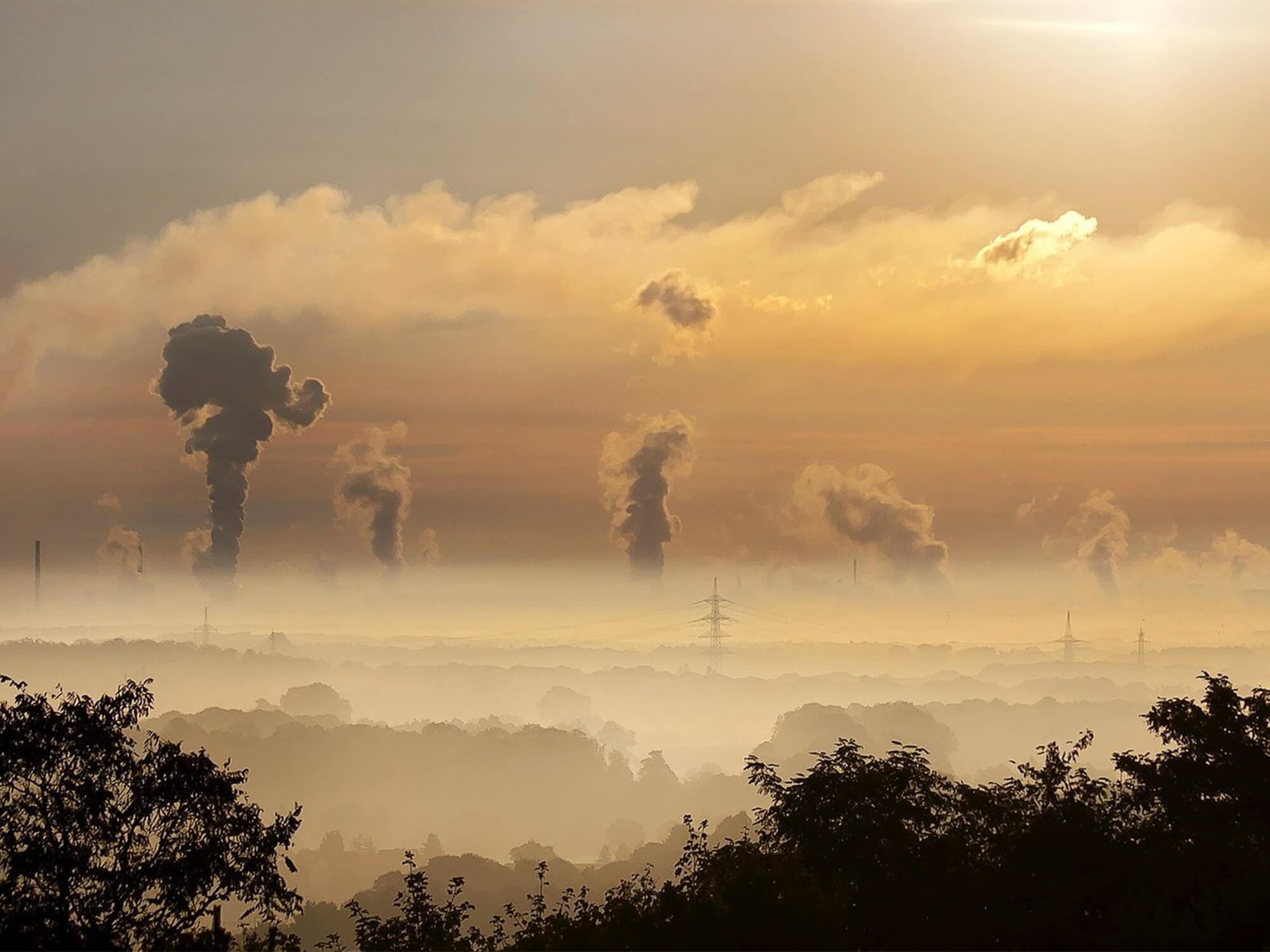 vapour rises from industrial chimneys and a haze covers the landscape