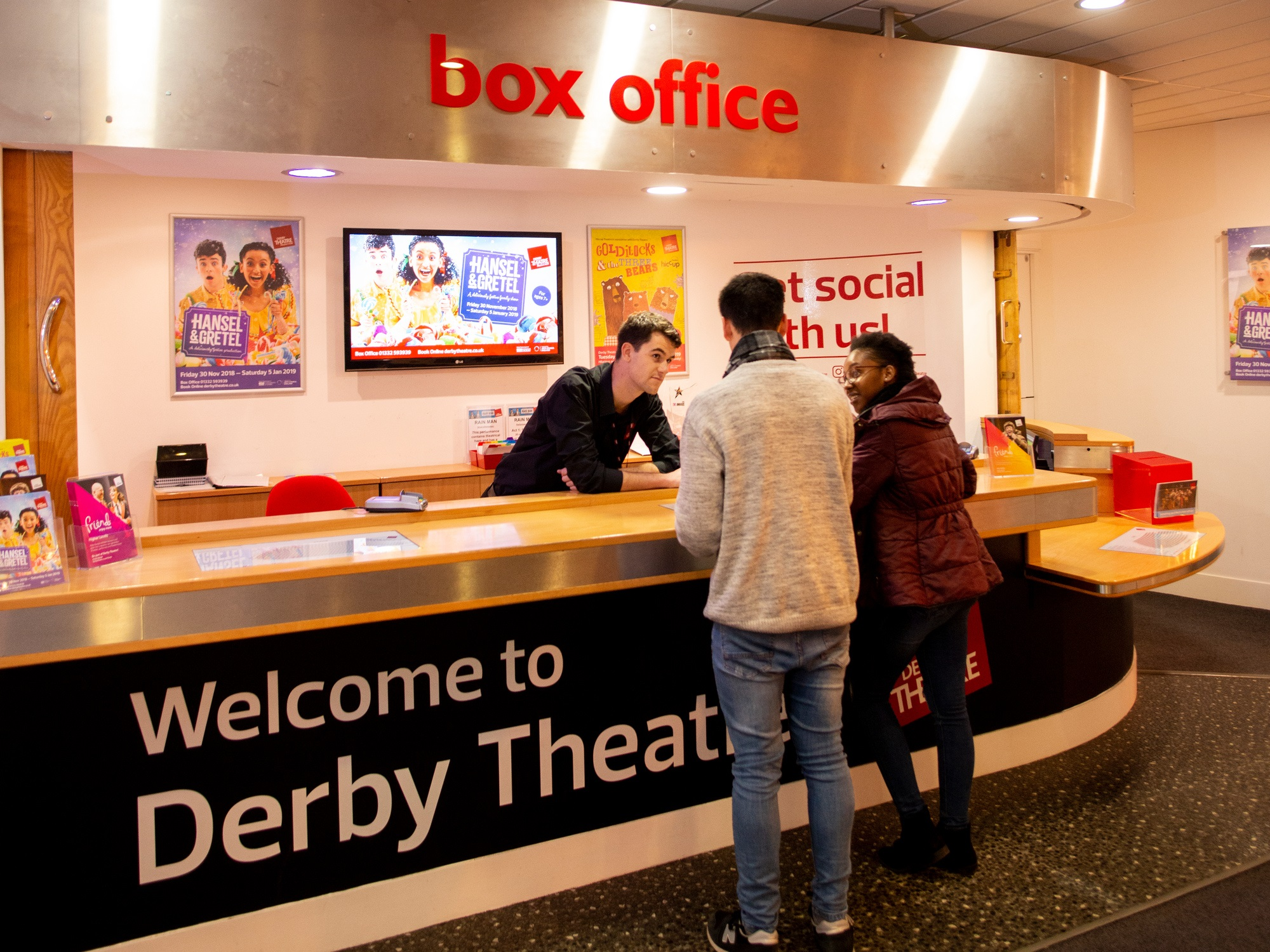 man and woman buying tickets at theatre box office