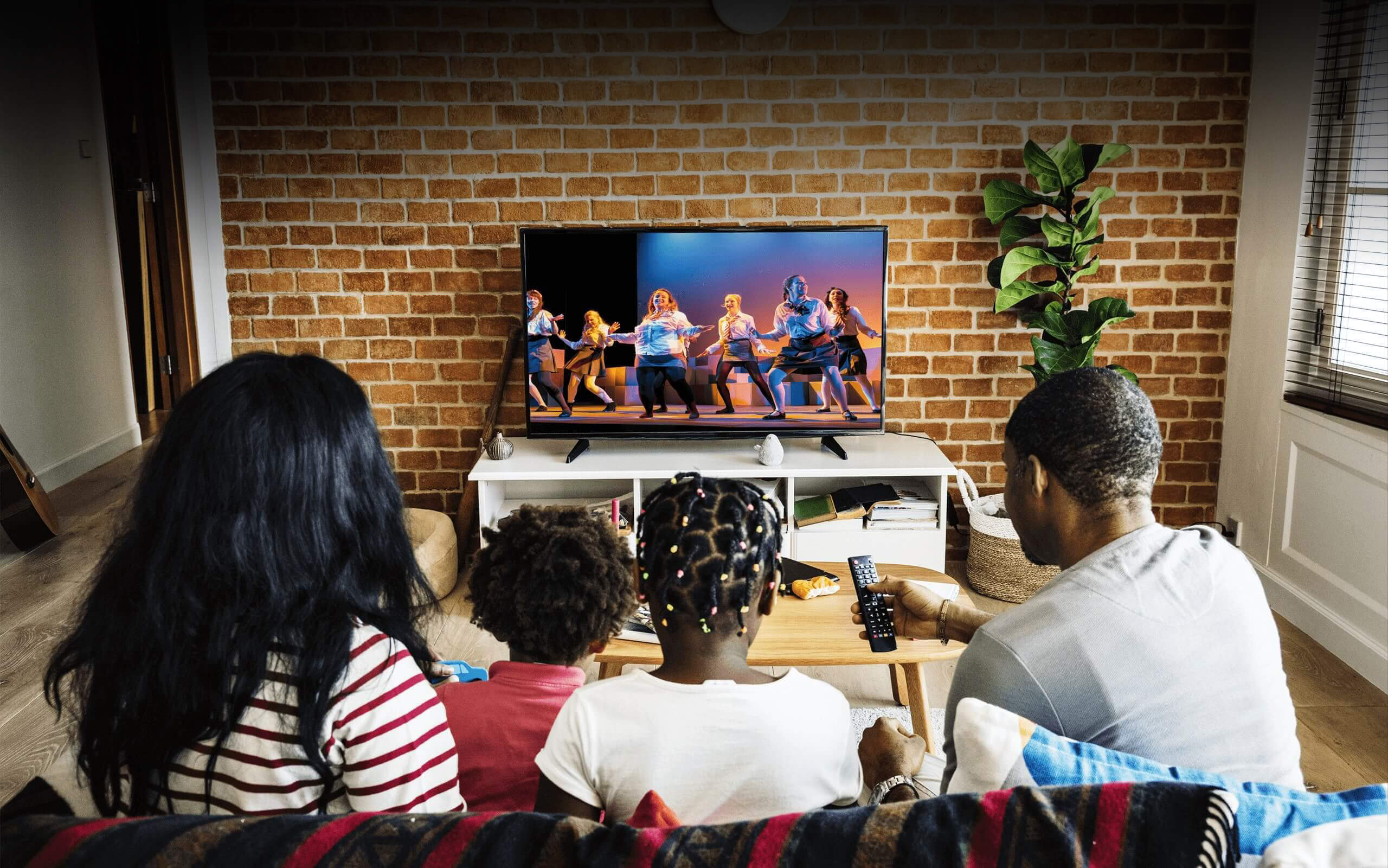 A family sat on a sofa watching TV