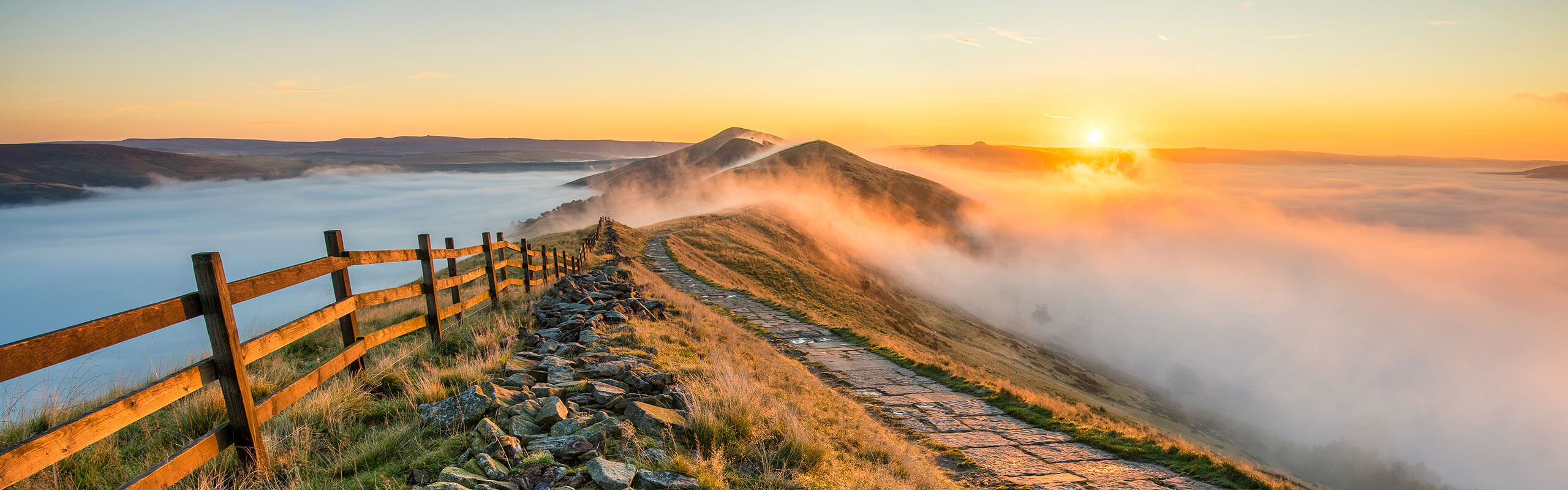 Walking path and fence running over hilltops, above the clouds, with sunrise in distance