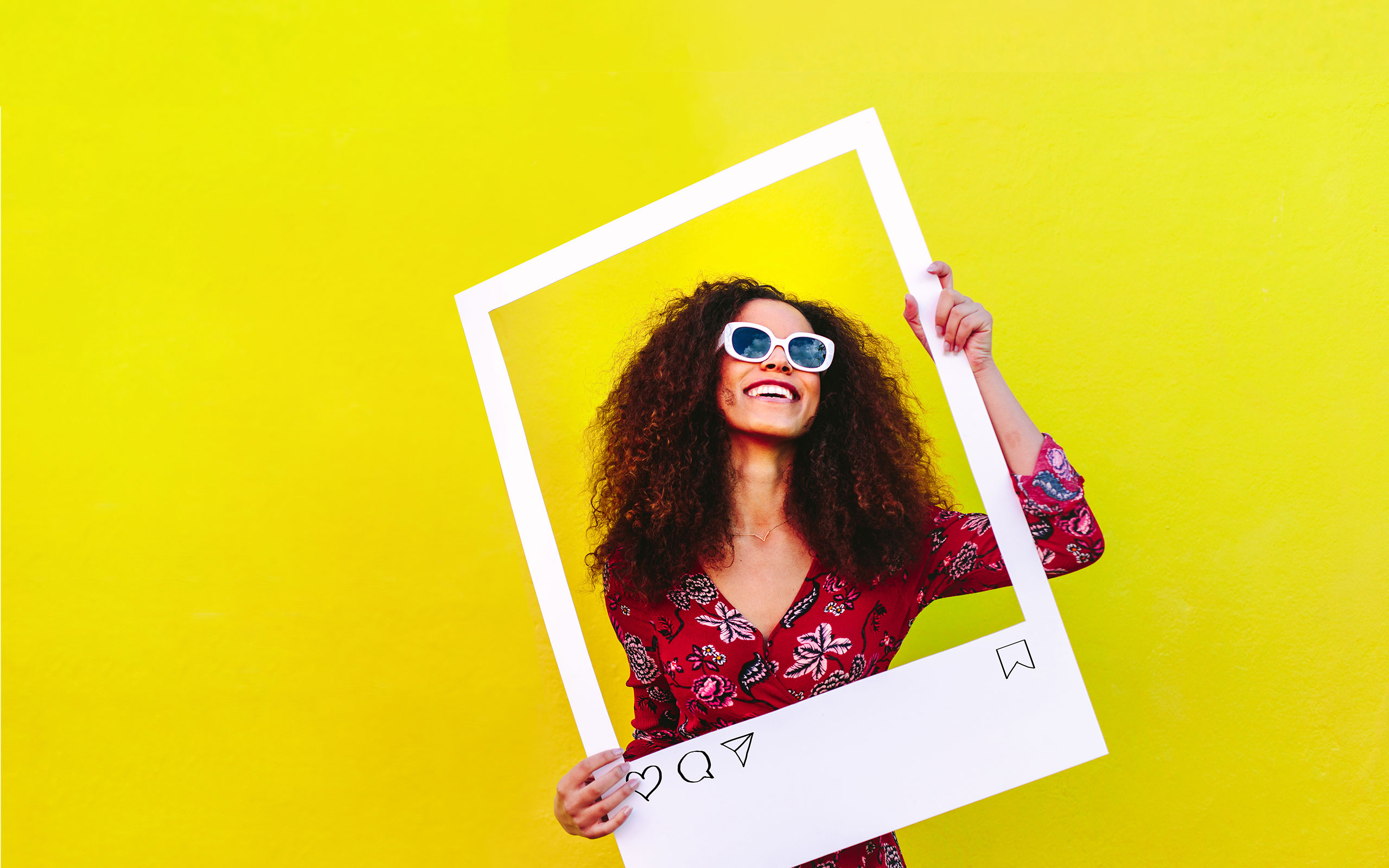 Woman wearing dress and sunglasses smiling within a large Polaroid frame cut-out that she's holding up