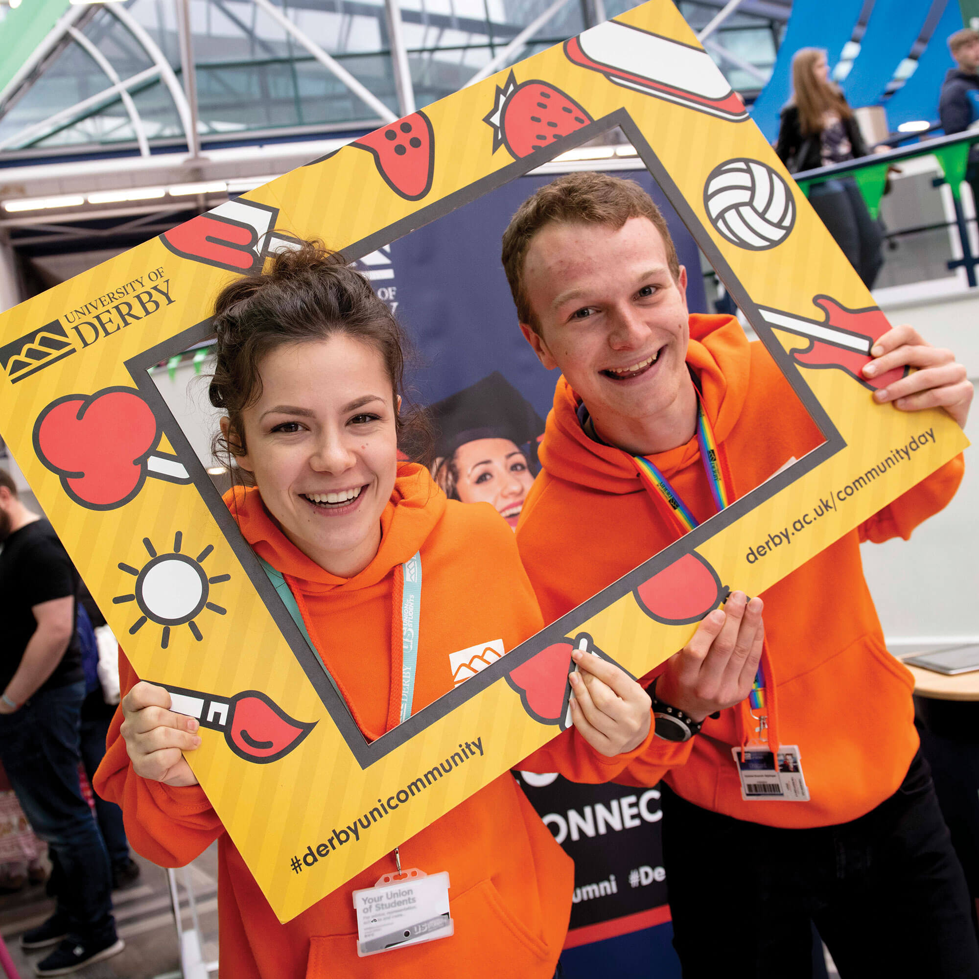 Two student ambassadors in orange hoodies smiling whilst holding polaroid-style frame around faces